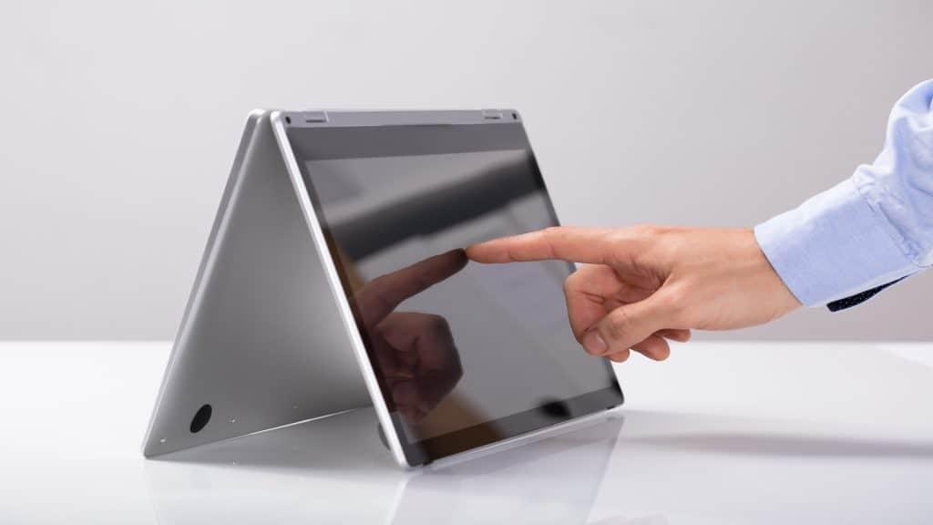 Detalhe de mão com o dedo na tela do notebook 2 em 1.