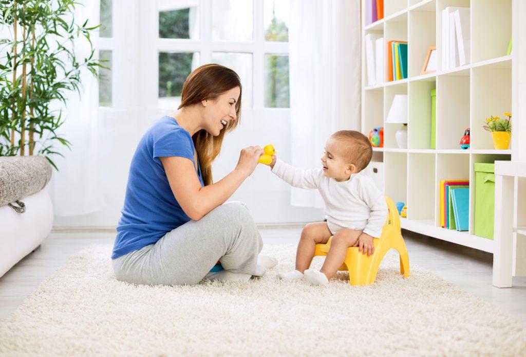 Mãe sentada no chão e bebê no troninho.