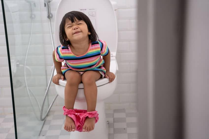 Criança sentada no vaso sanitário.