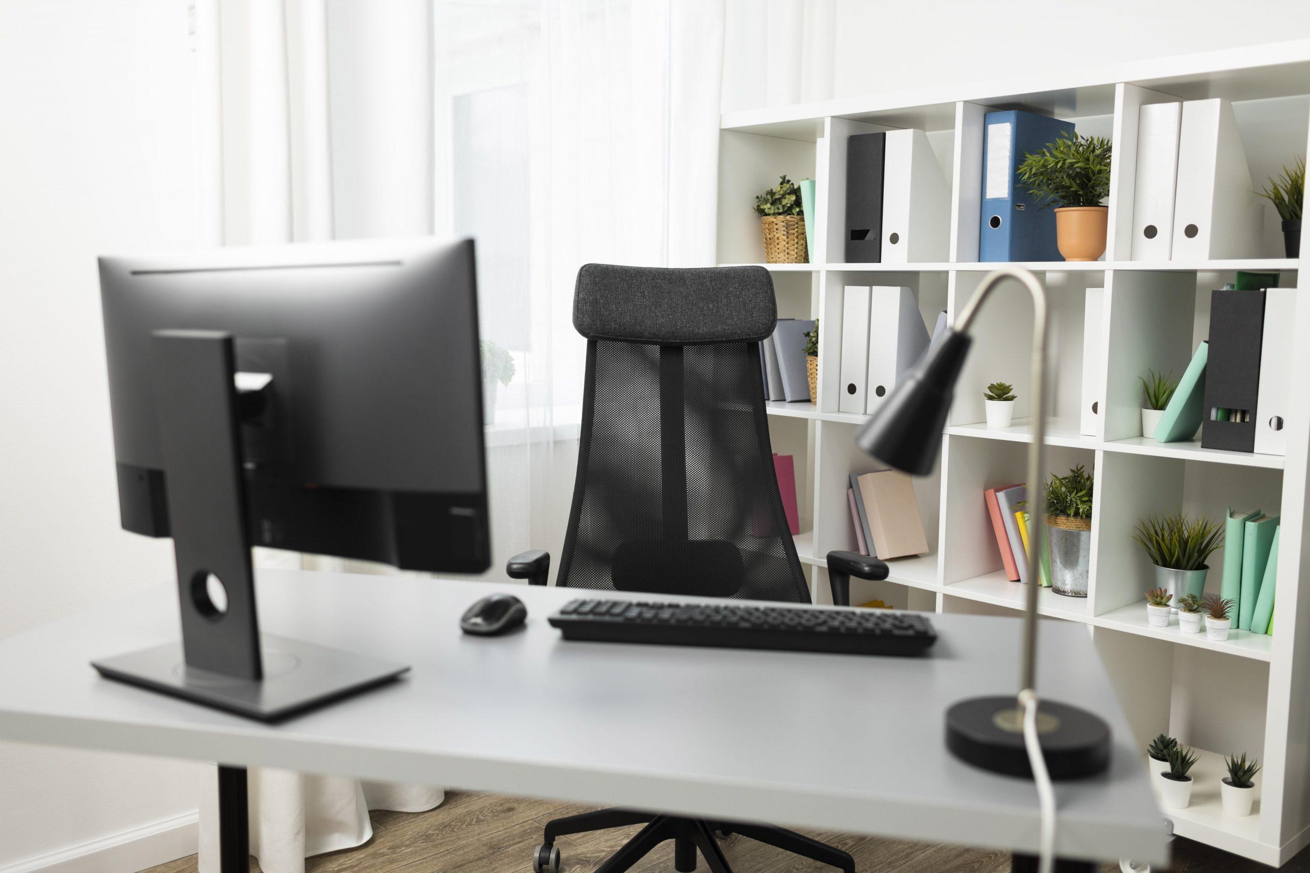 Um local de trabalho com uma mesa, computador, iluminária e cadeira giratória. Ao fundo, existe um armário com plantas, livros e pastas.