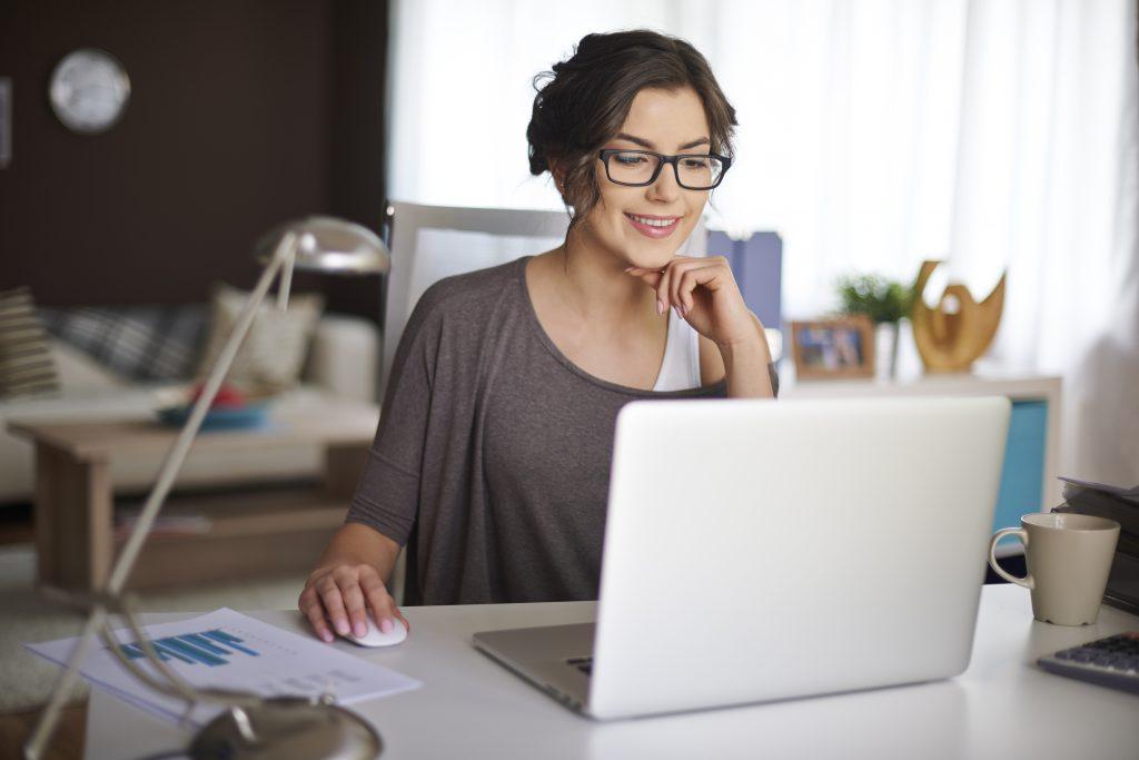 Uma mulher em uma sala de trabalho, sentada em uma cadeira de escritório. Ela observa o notebook em uma mesa com acessórios como papéis, caneca de café e luminária.