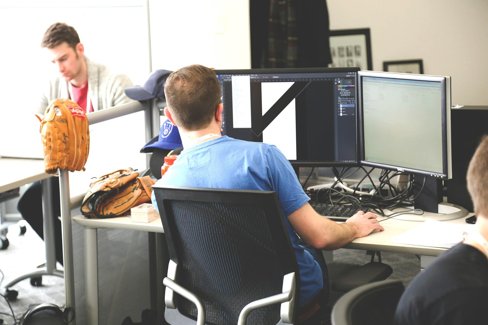 Um homem em um escritório. Ele está de costas, sentado numa cadeira giratória, em frente ao computador. A cadeira ergonômica