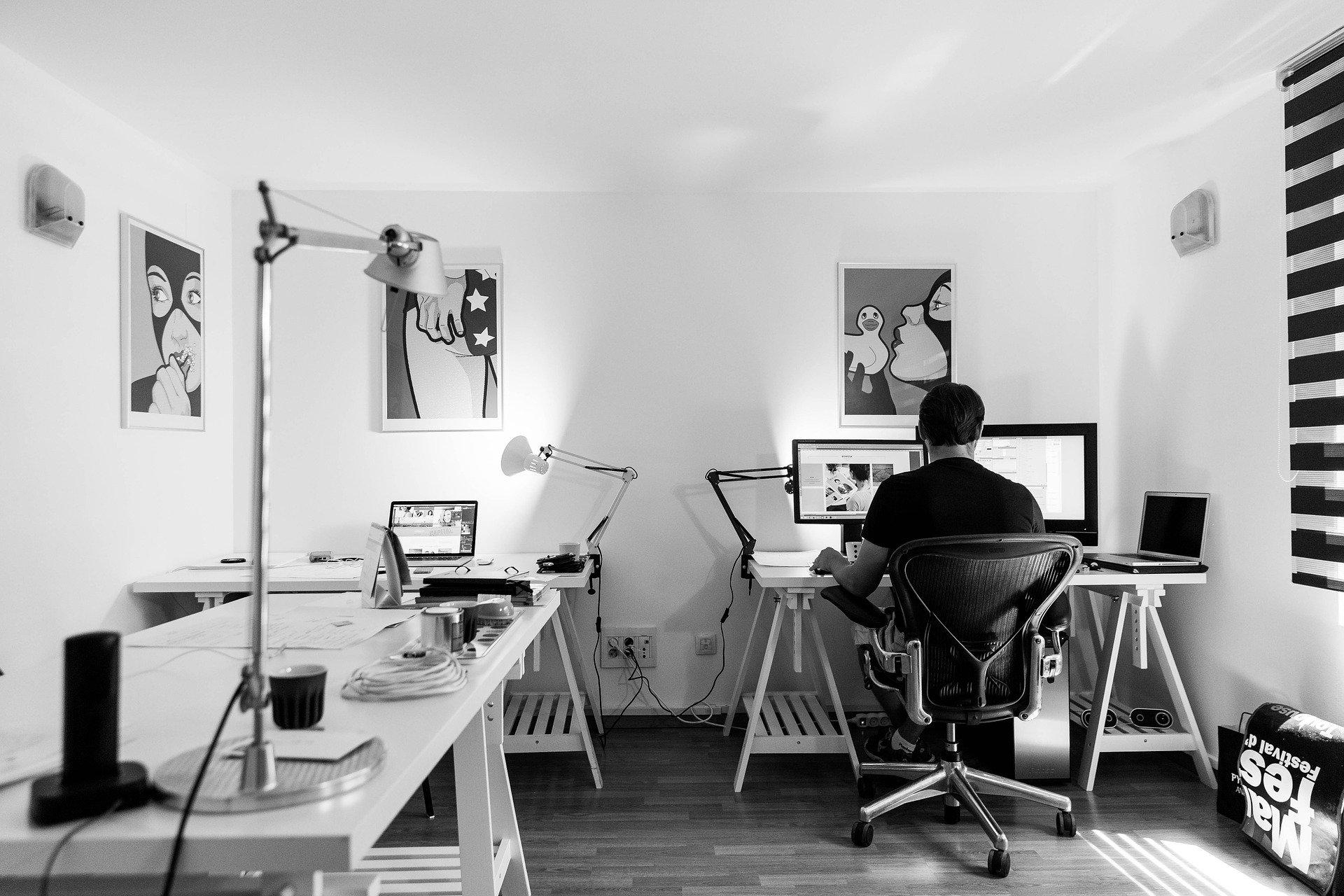 Um escritório onde um homem está trabalhando. Ele está sentado numa cadeira giratória e, ao redor, estão vários computadores. Na parede existem quadros. O ambiente também tem outras mesas de trabalho, porém sem pessoas.