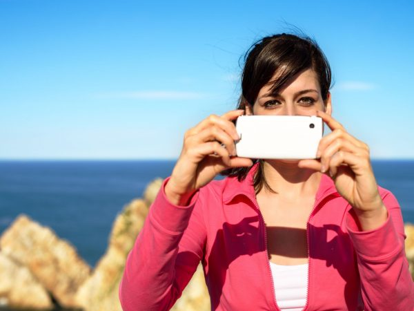 19637389 – tourist woman taking photo with cellphone and having fun on summer travel. brunette girl smiling and taking snapshot on coast landscape.