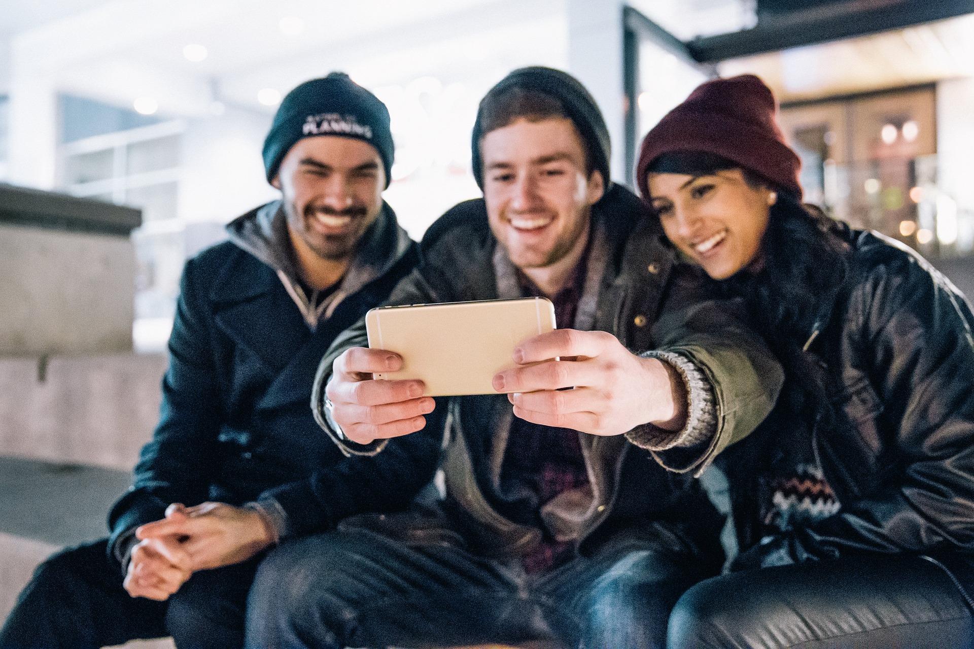 Três pessoas tirando selfie.