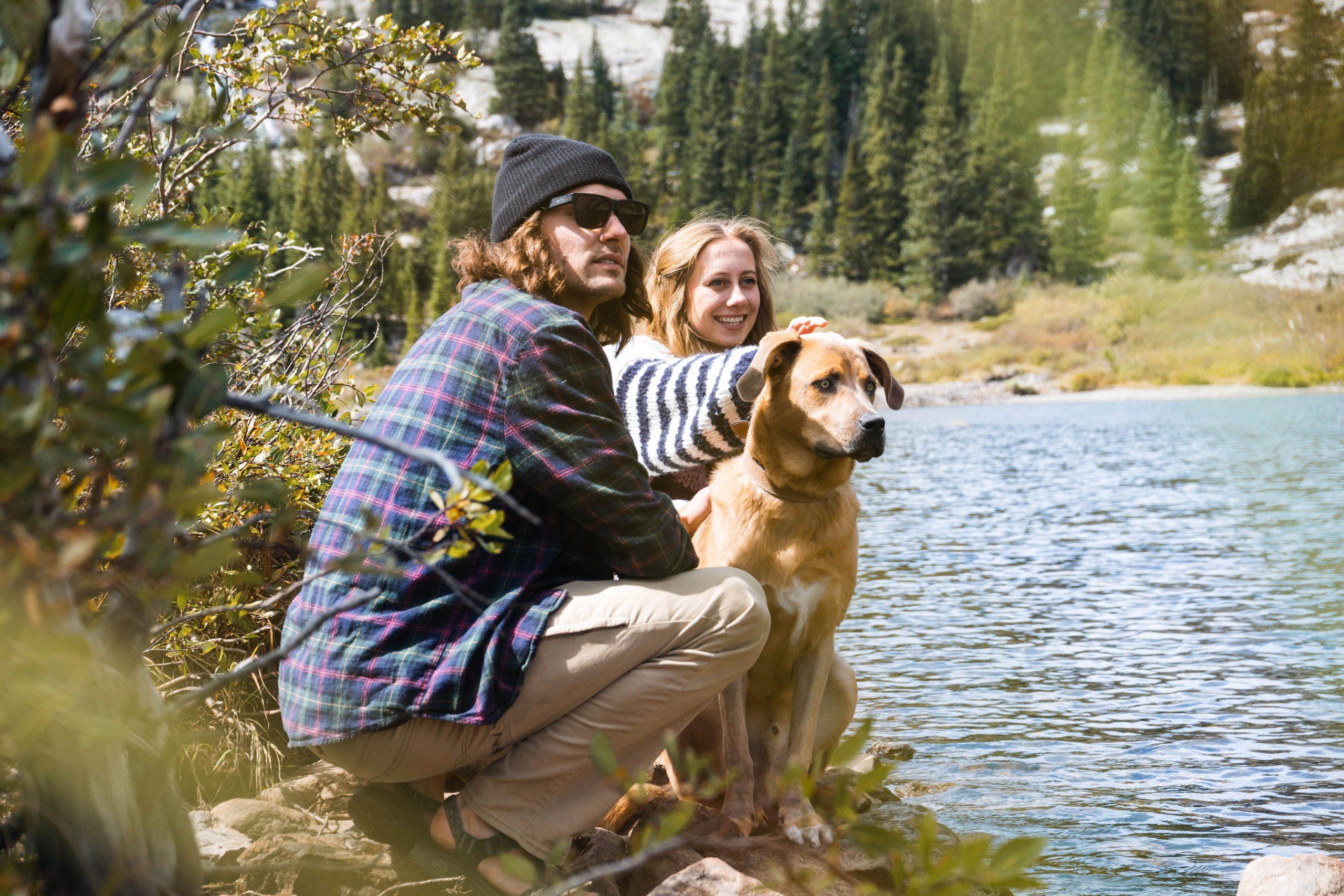 Imagem de casal com seu cachorro na beira do rio