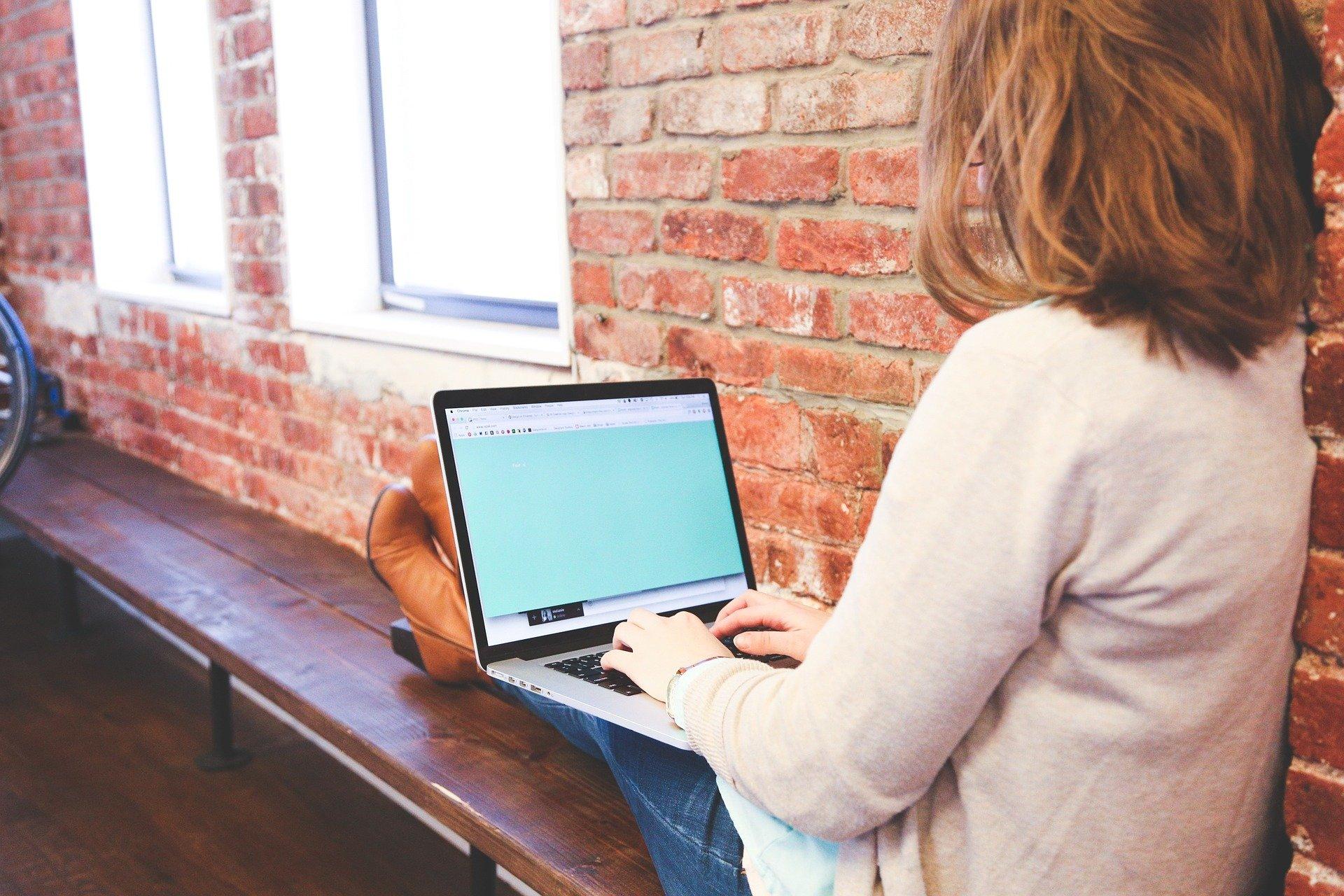 Mulher sentada com notebook no colo.