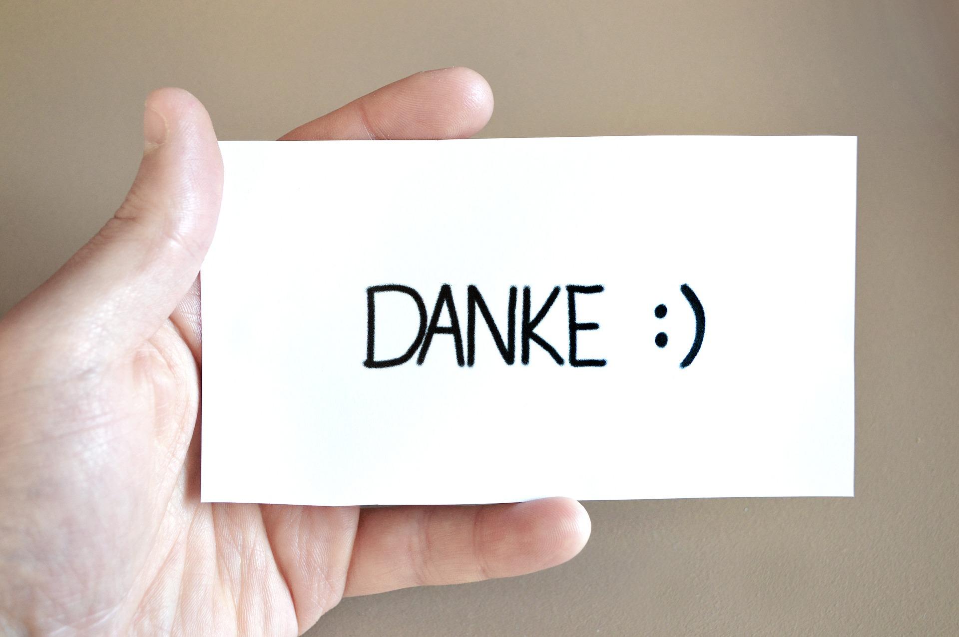 """Mãe segurando cartão escrito a palavra """"Danke""""."""
