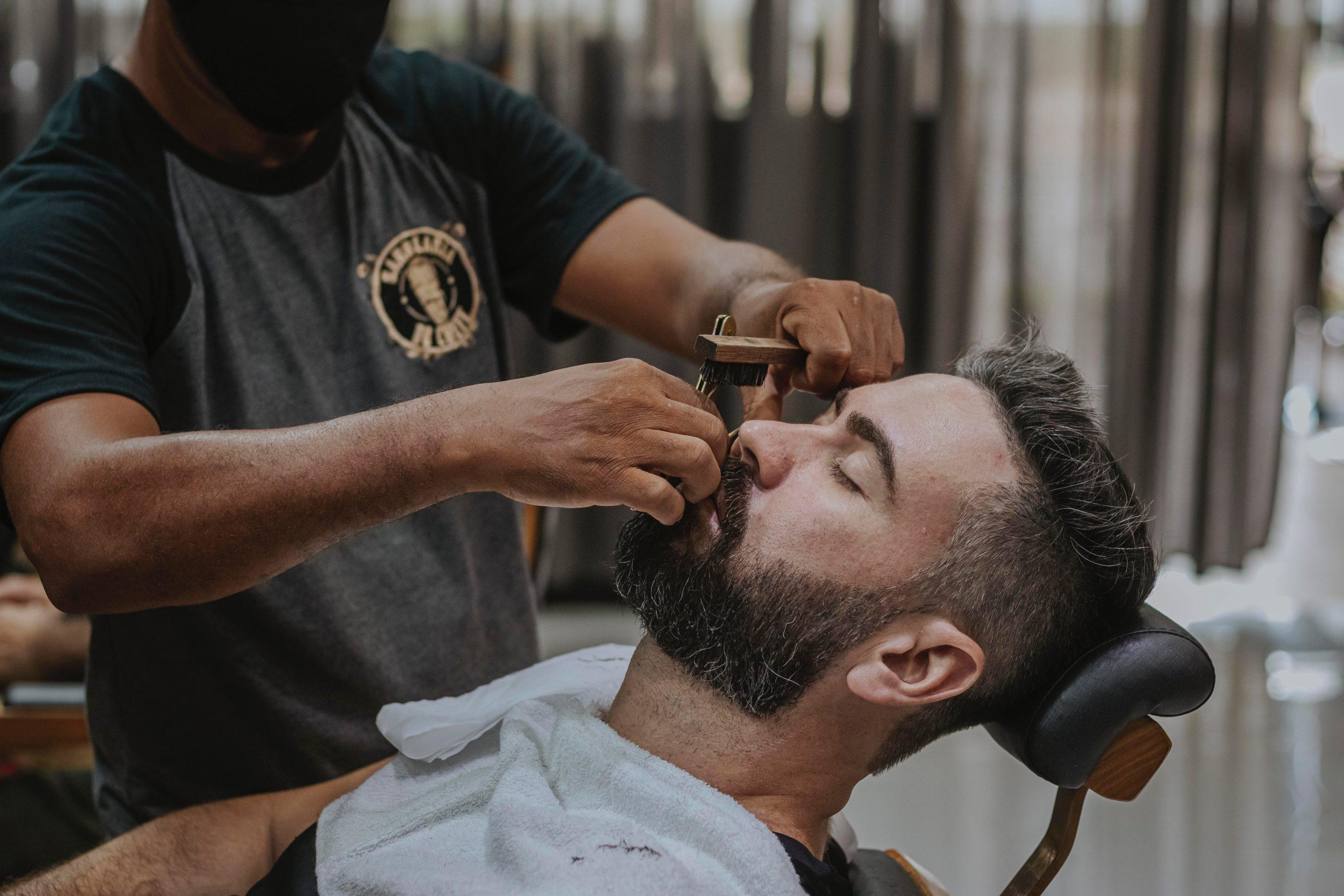 Barbeiro fazendo a barba de cliente