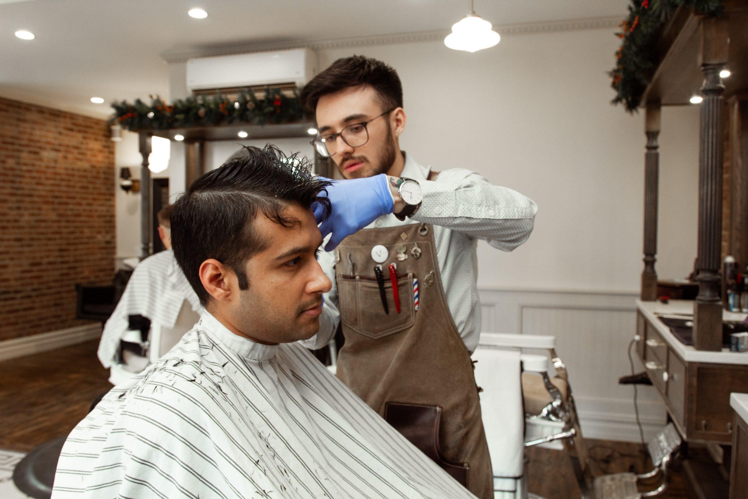 Barbeiro de luva azul e macacão cortando cabelo de cliente