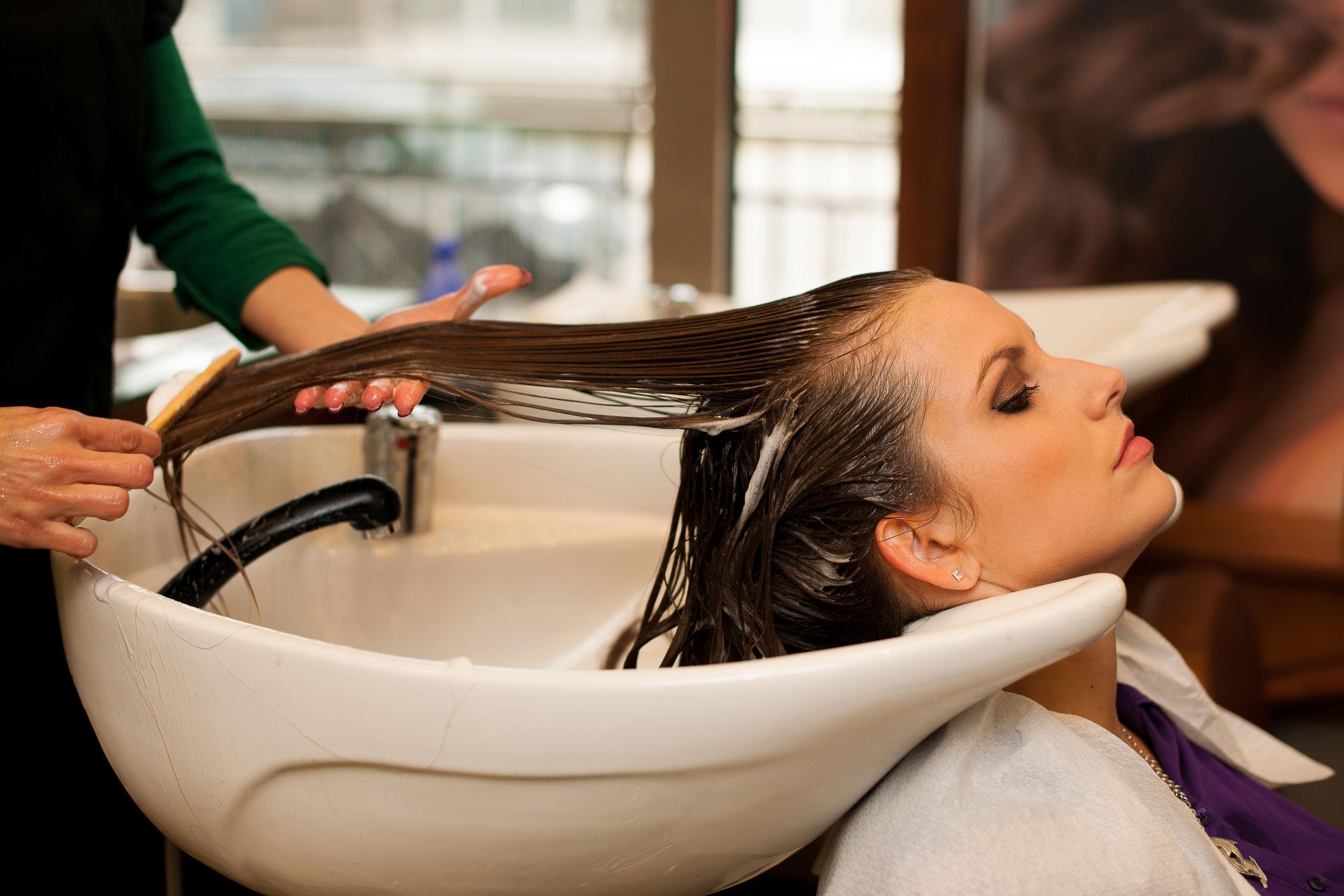 mulher em salão de beleza recebendo tratamento ensinado no curso de cabeleireiro