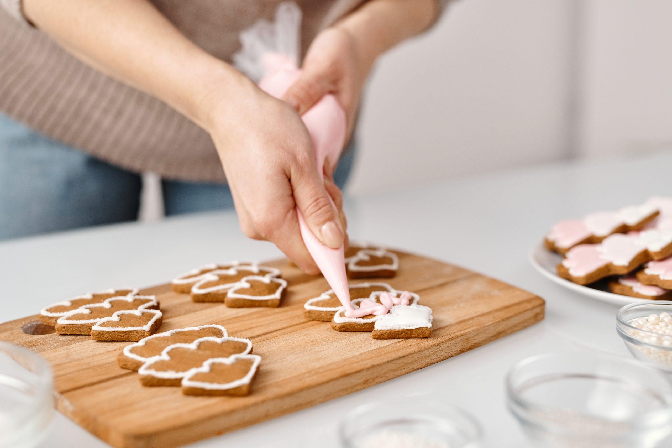 Imagem de uma pessoa confeitando biscoitos.