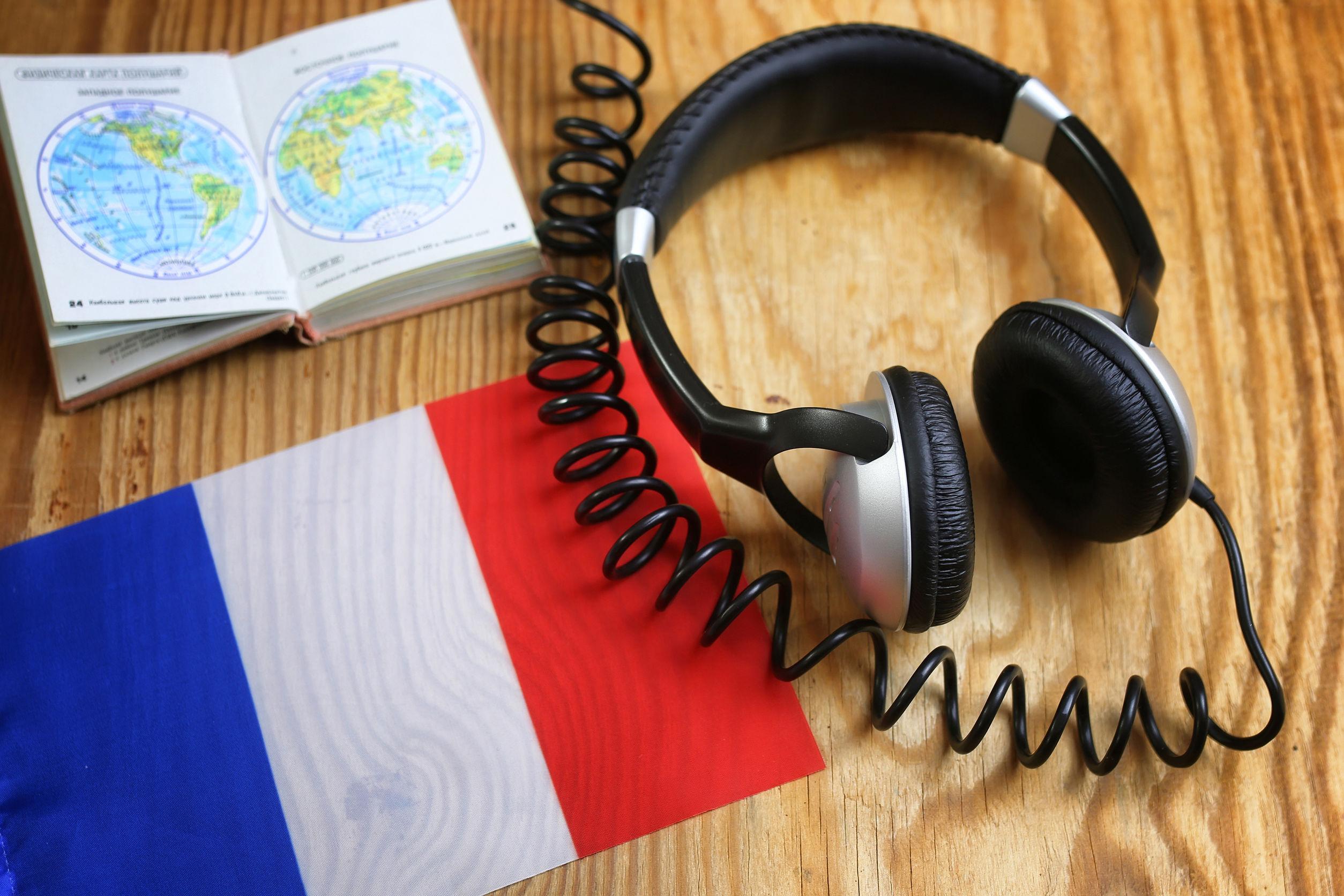 fone de ouvido em uma mesa com bandeira francesa e dicionário para o curso de francês