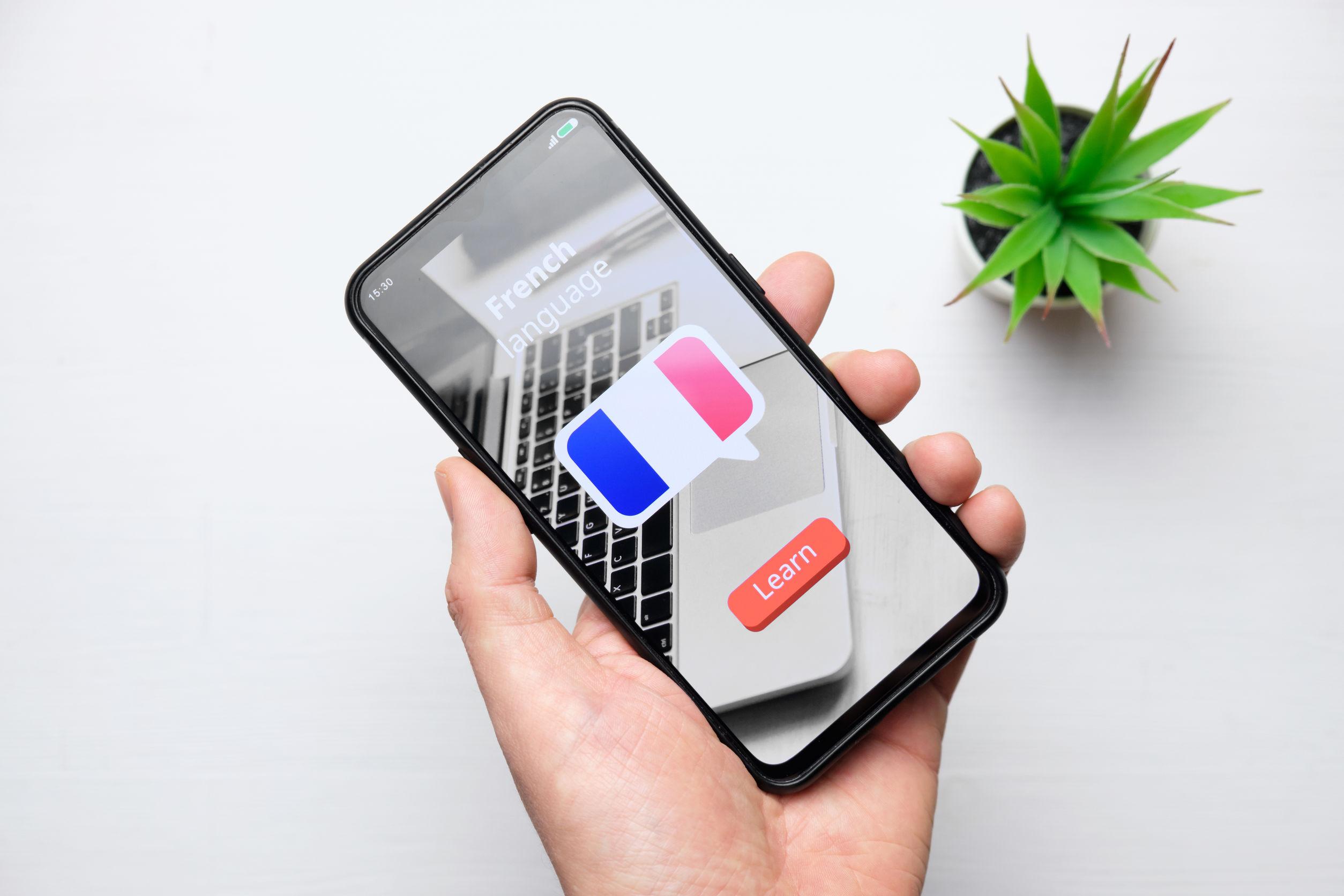 homem segurando smartphone na tela inicial do curso de francês