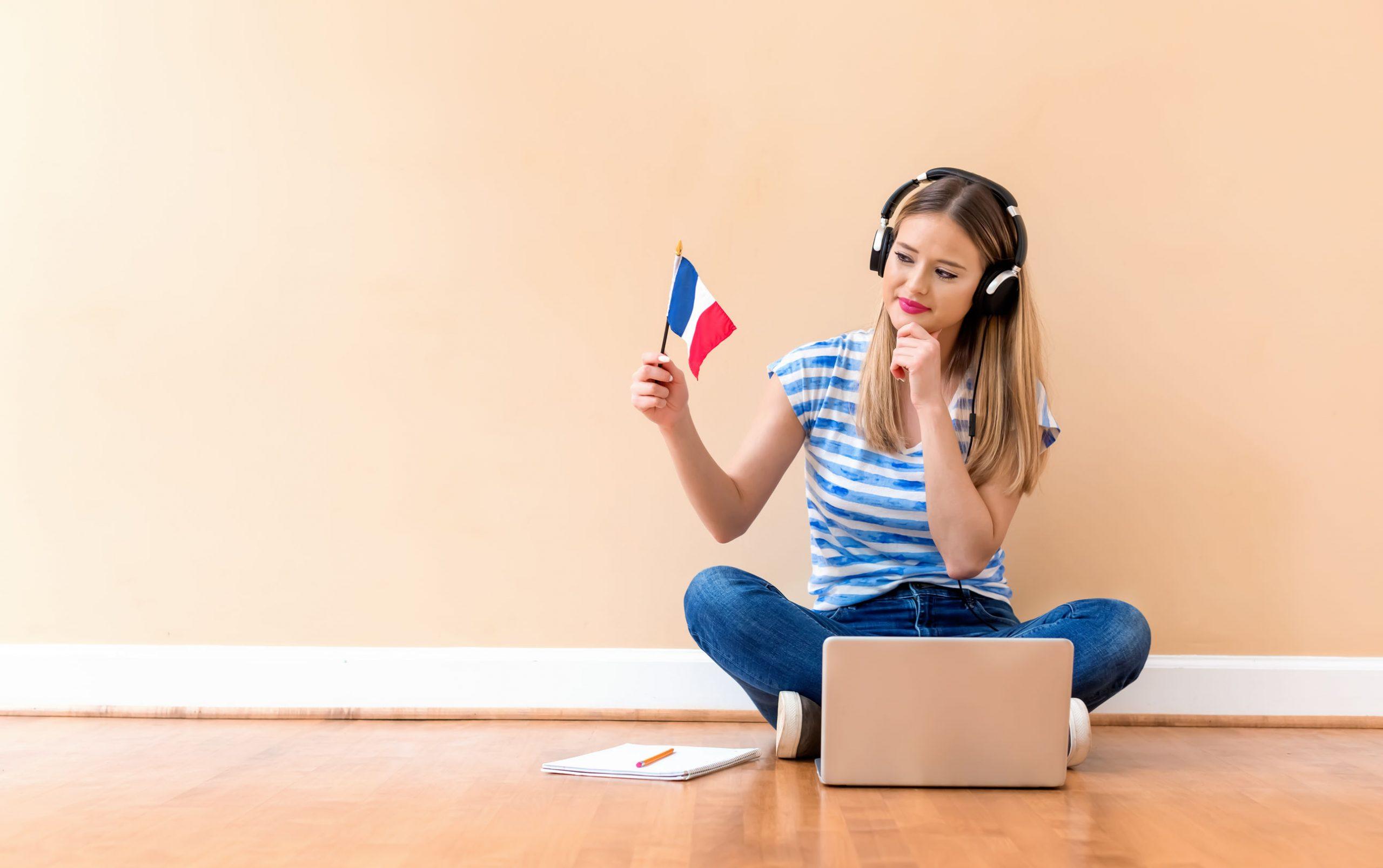 moça sentada no chão fazendo curso de francês pelo computador