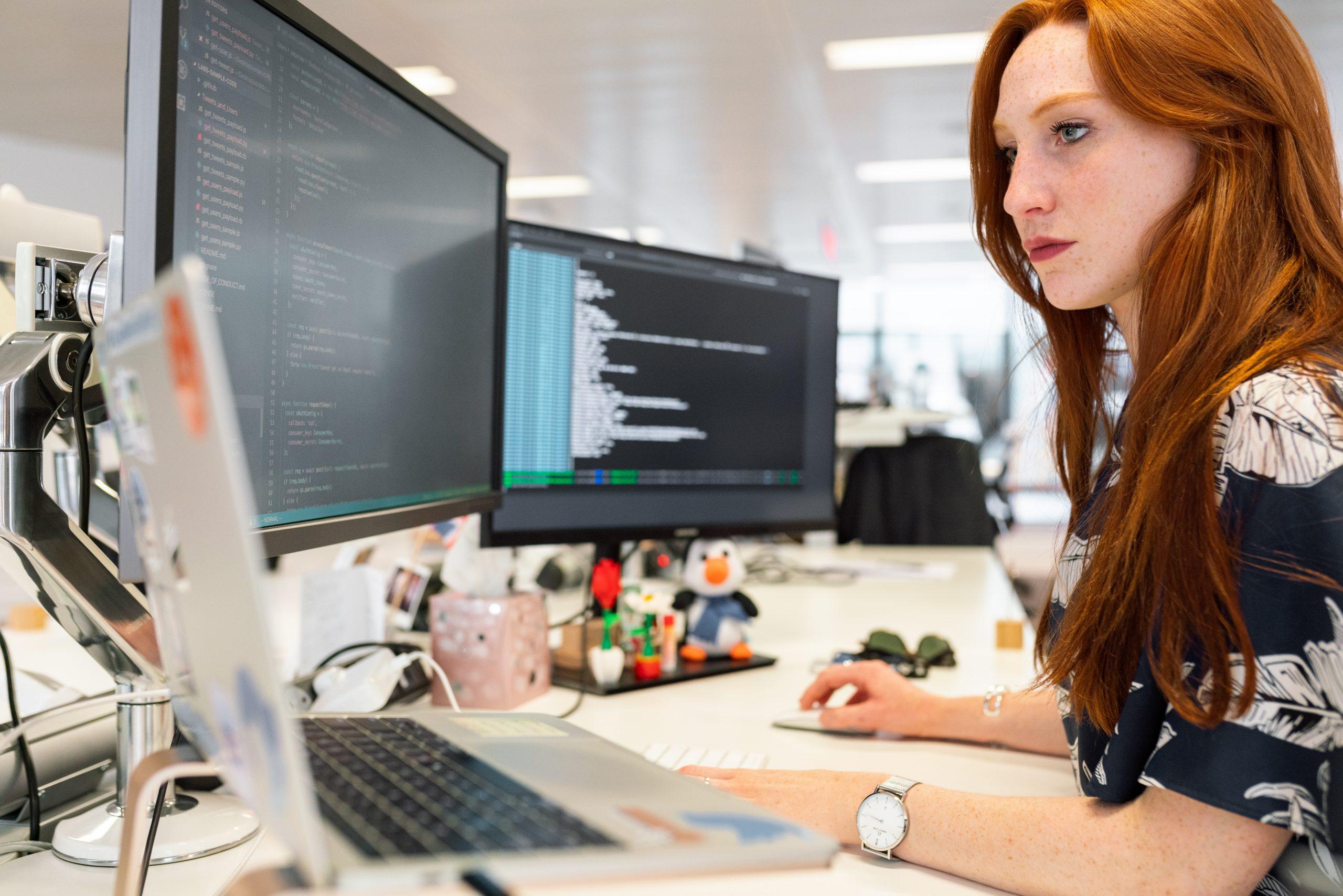 Mulher trabalhando com dois monitores de computador e um notebook na mesa.