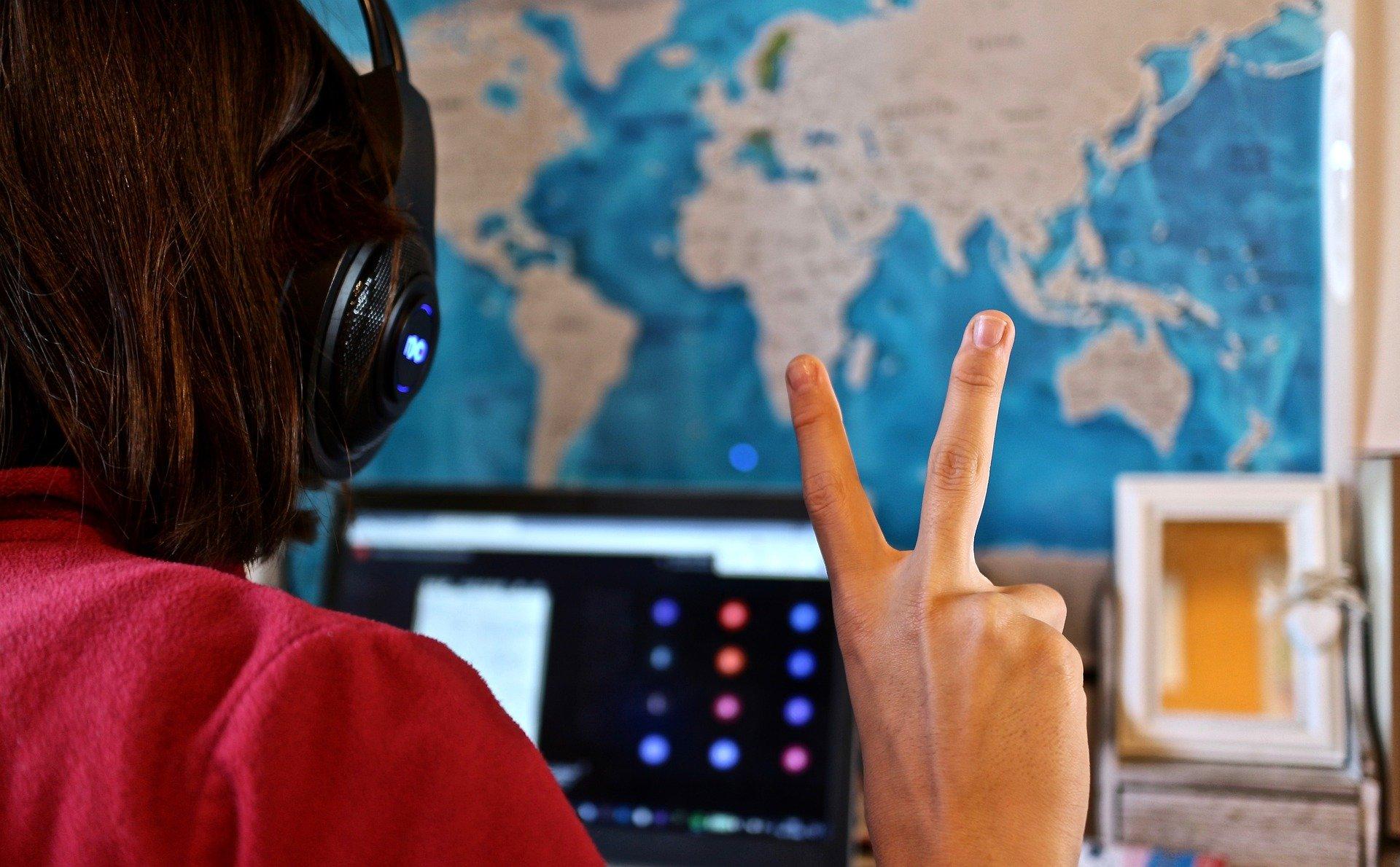 Pessoa estudando online com fone de ouvido e notebook.