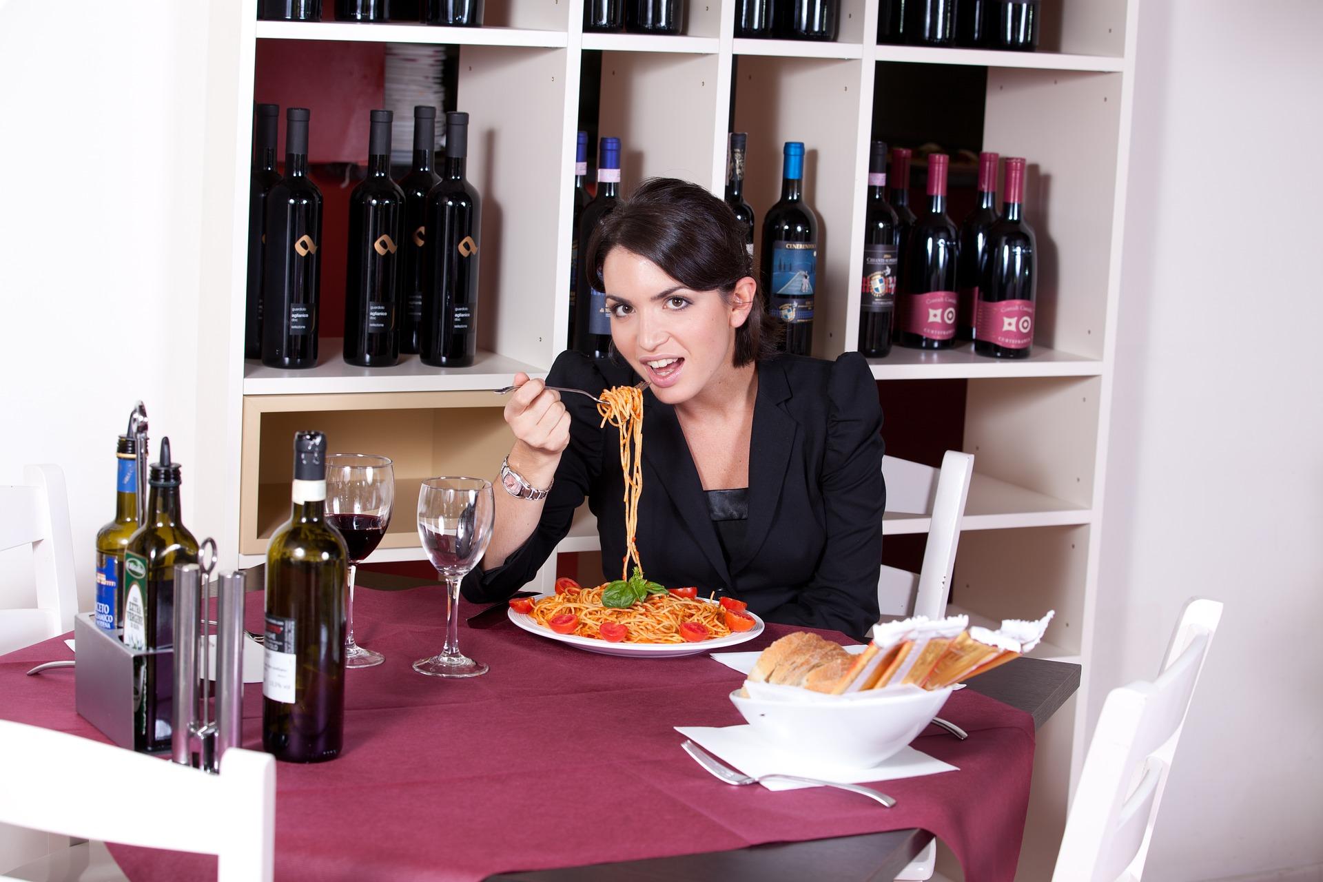 Mulher comendo comida italiana com adega de vinhos atrás.