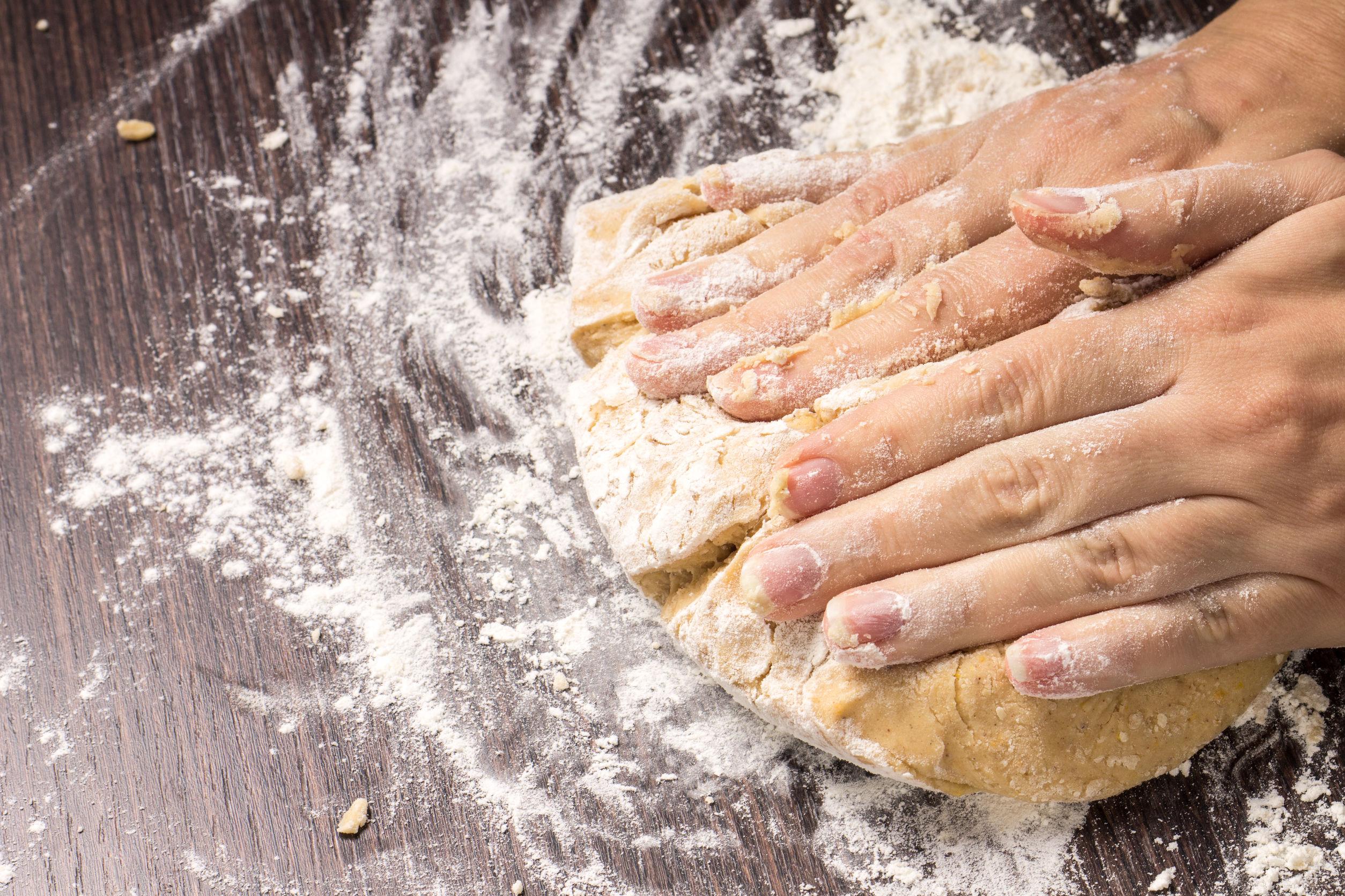Mãos em closeup sovando a massa em um curso de panificação