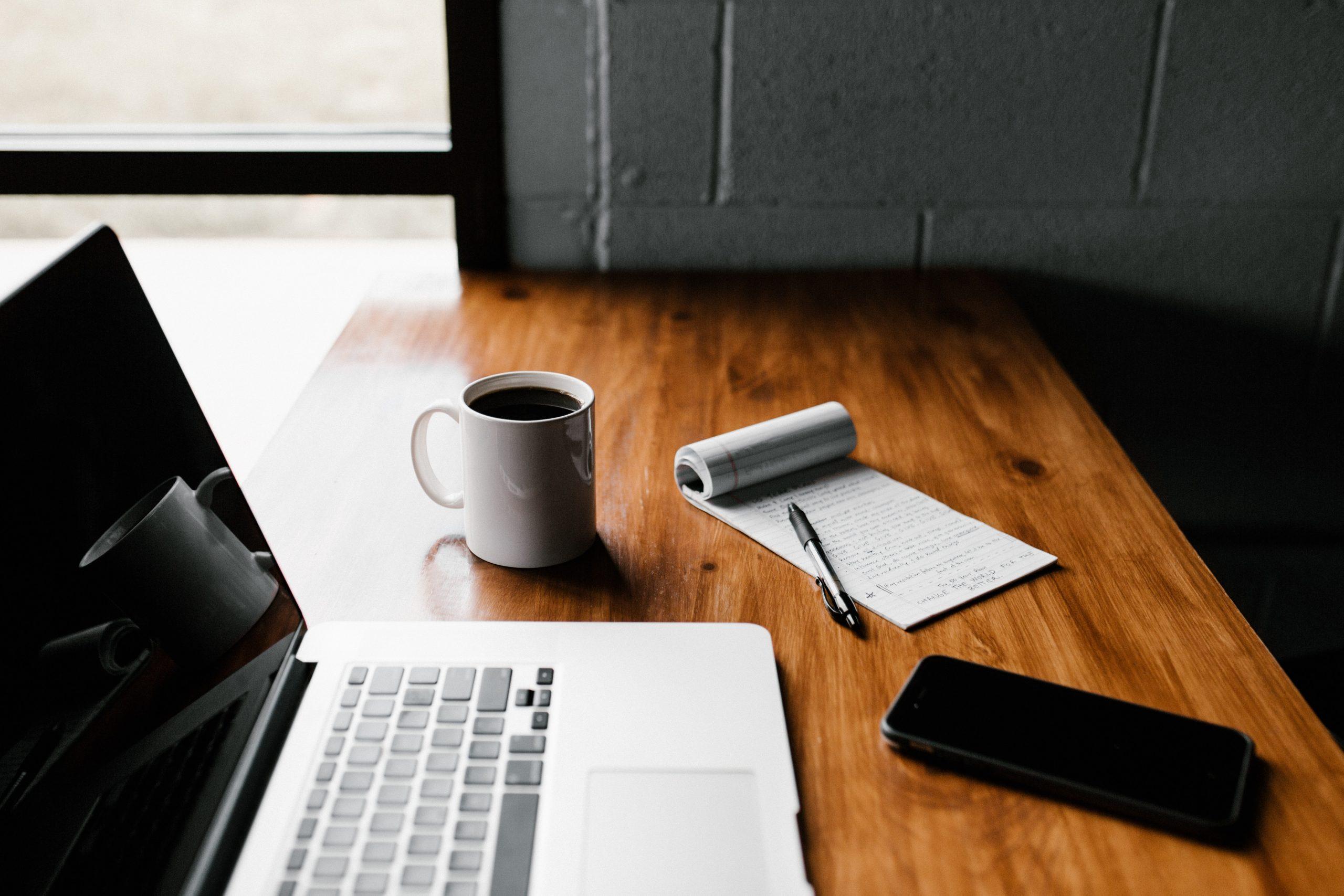 Notebook sobre a mesa ao lado de bloco de notas, caneta, celular e xícara de café