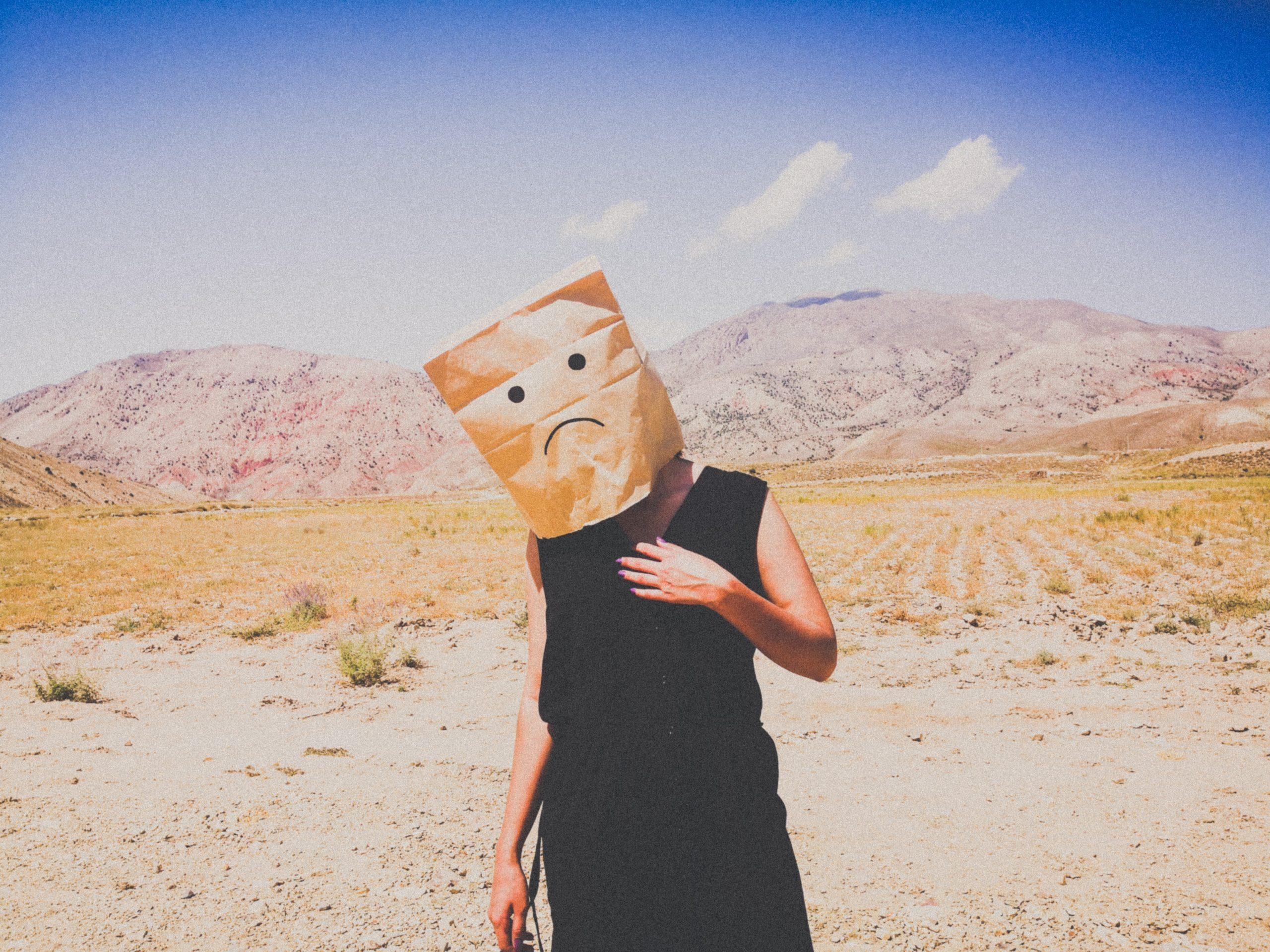 Imagem de uma pessoa com saco de pão com expressão triste na cabeça