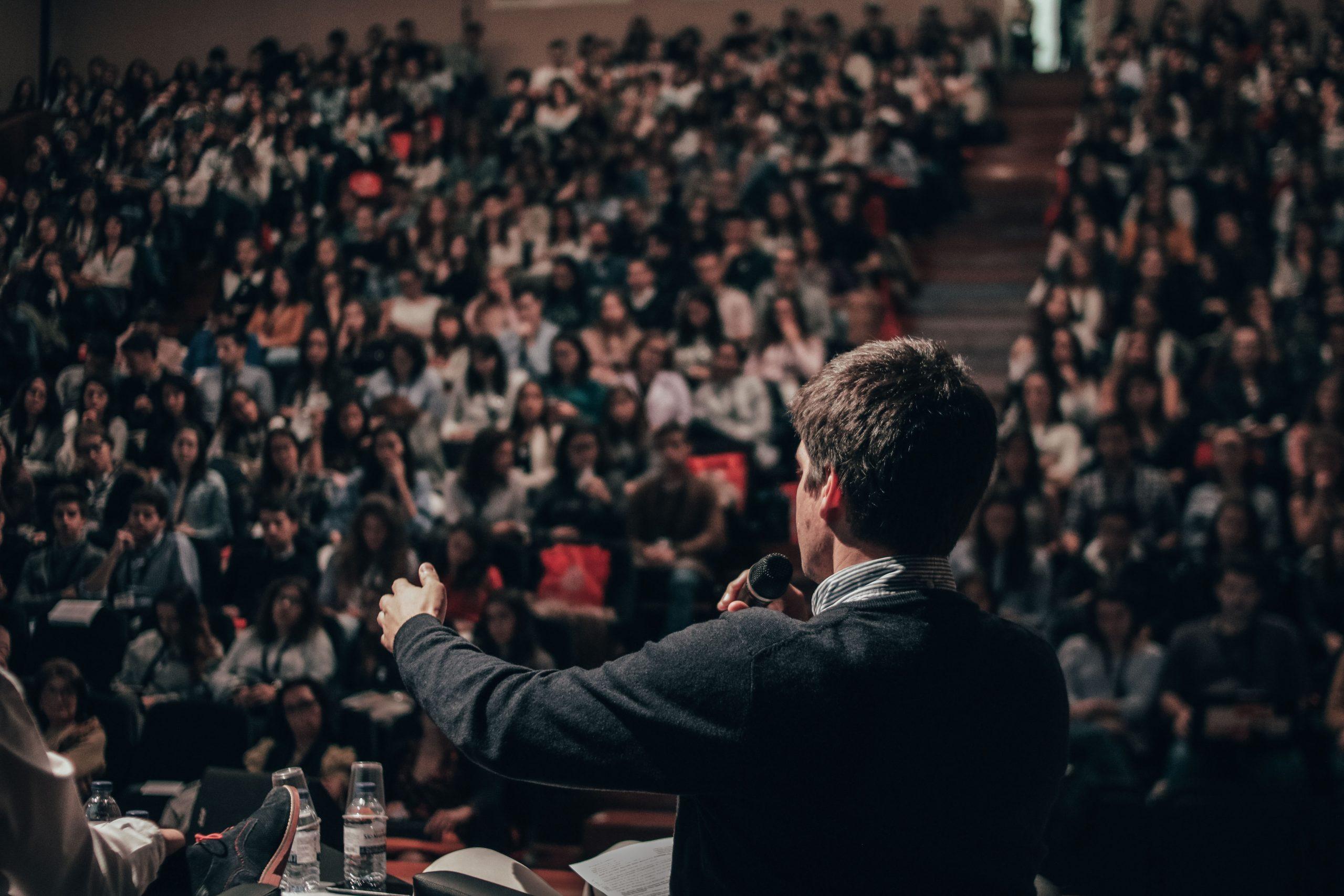 Homem de costas palestrando para uma grande audiência.