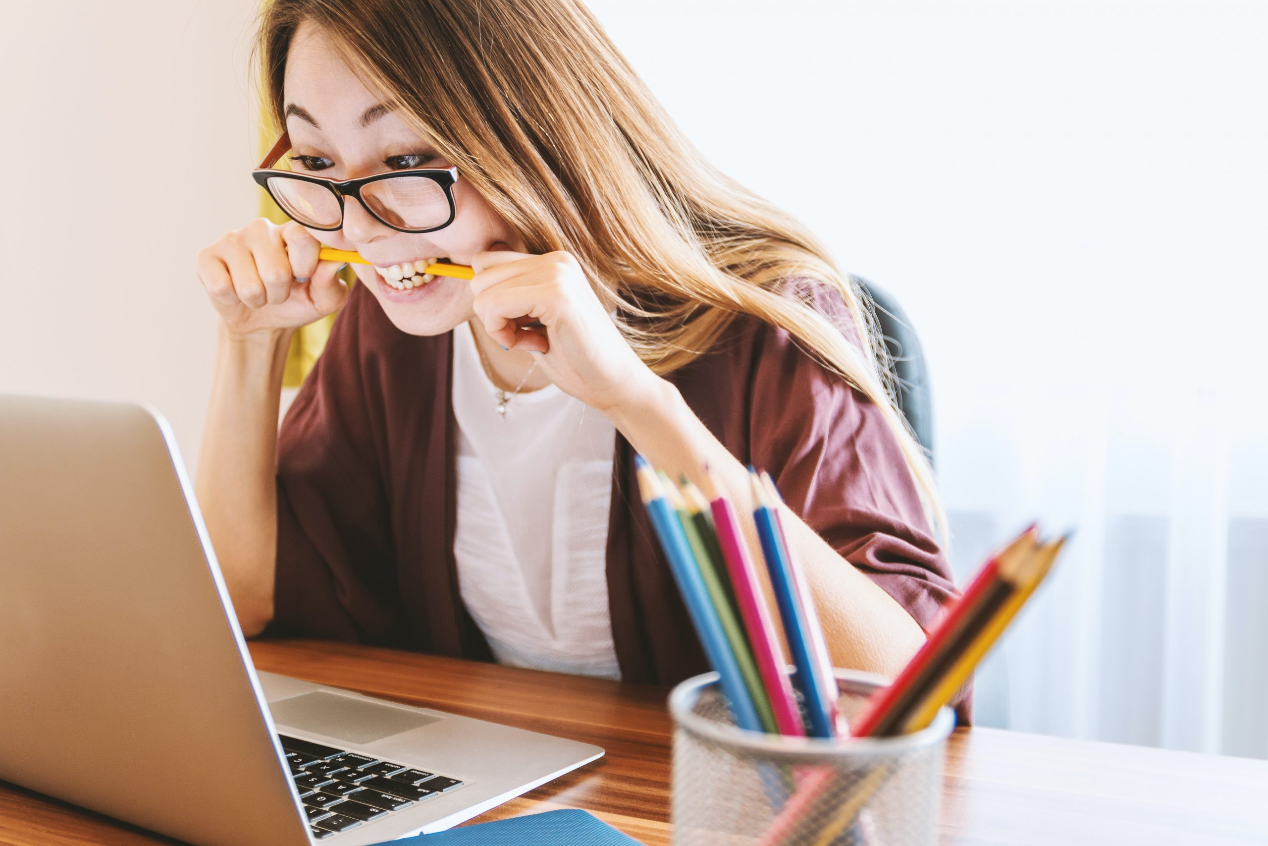 Imagem de uma mulher mordendo um lápis em frente ao computador.
