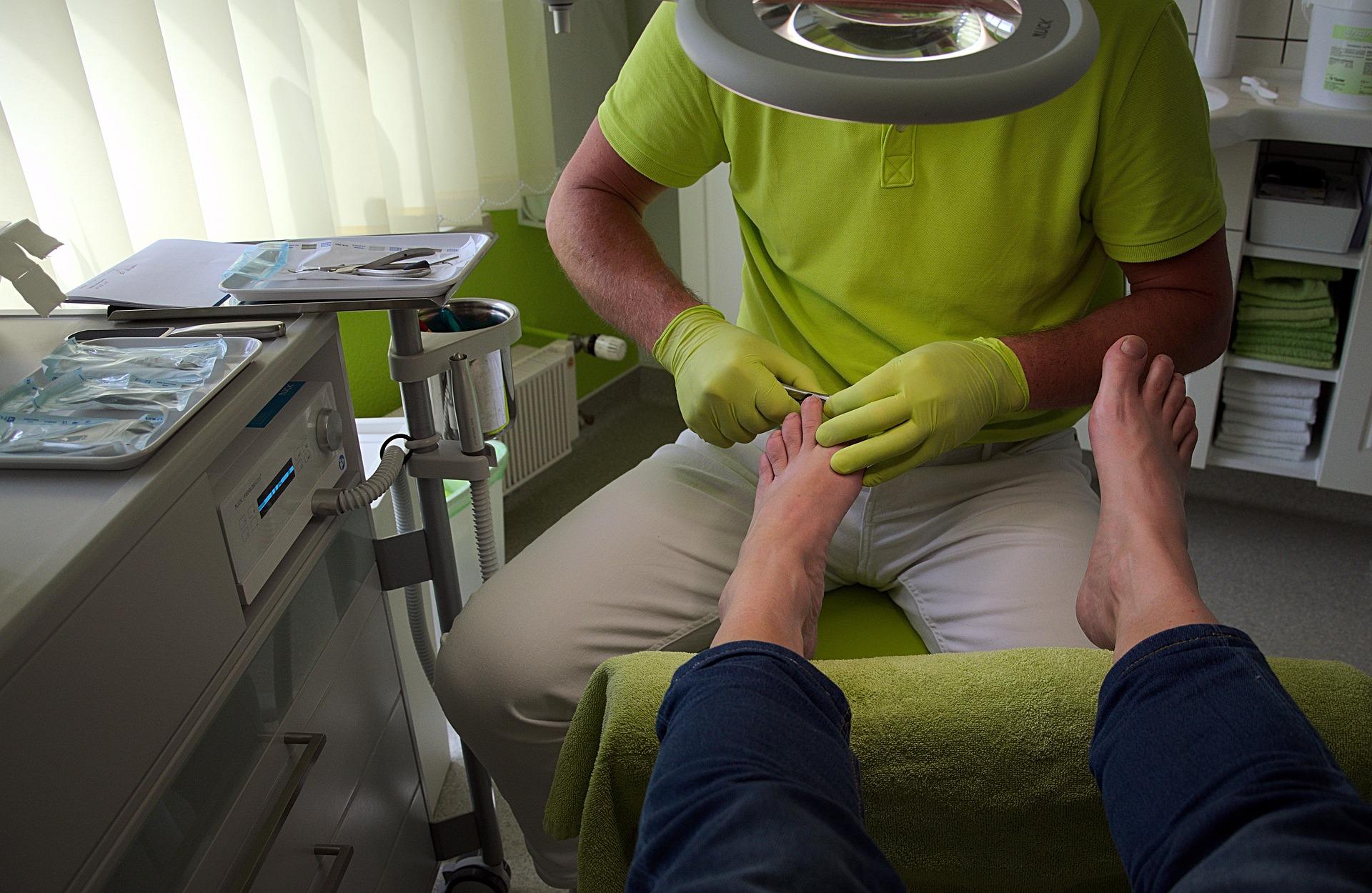 Podólogo cuidando do pé de cliente.