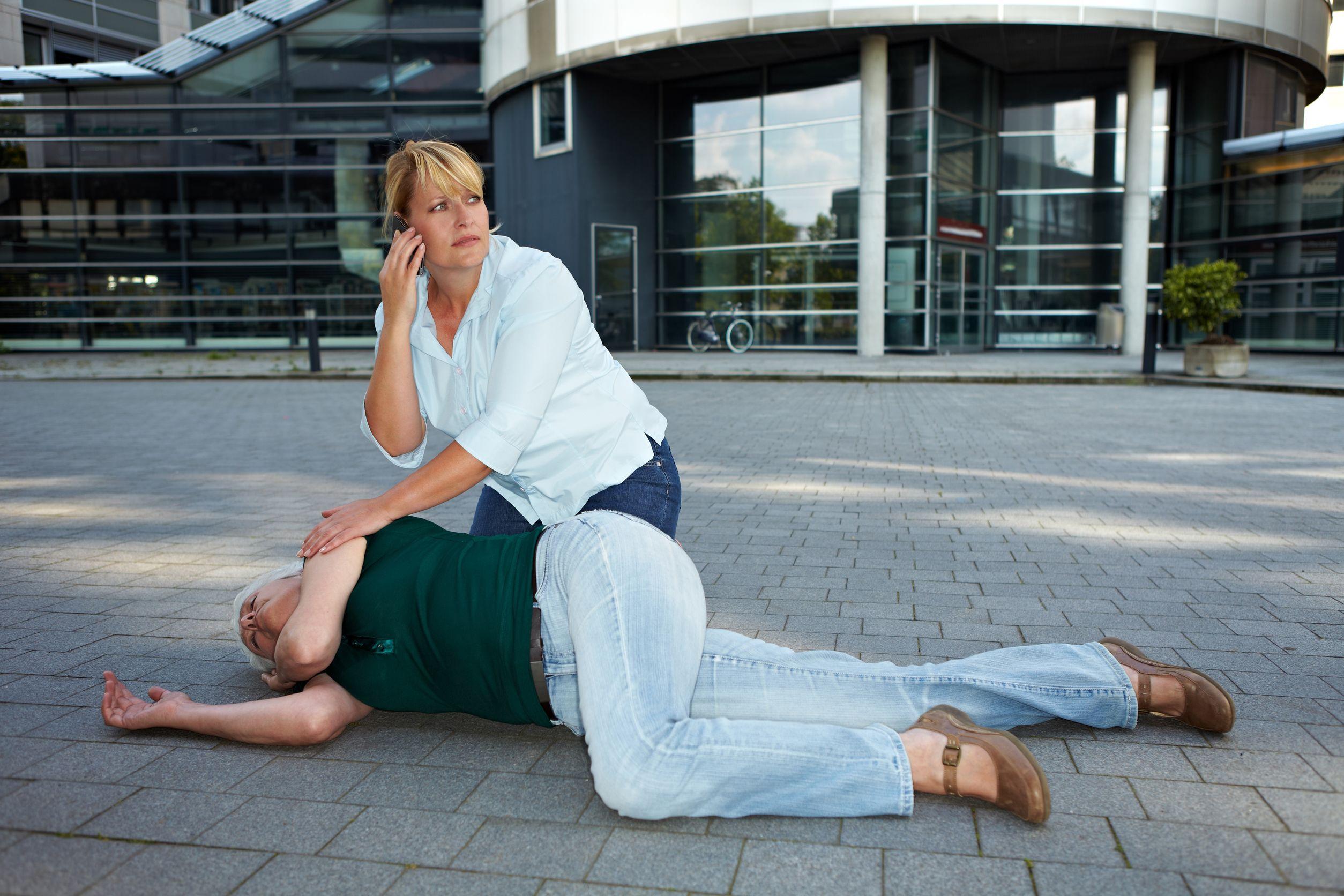 mulher ajudando uma senhora caída com as técnicas de primeiros socorros