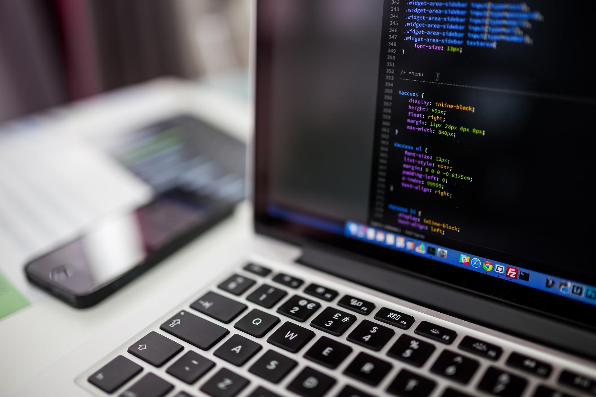 Notebook com códigos de programação aparecendo na tela.