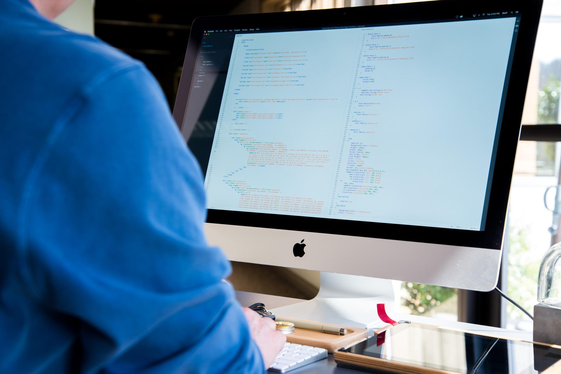 Homem programando em um Macbook.