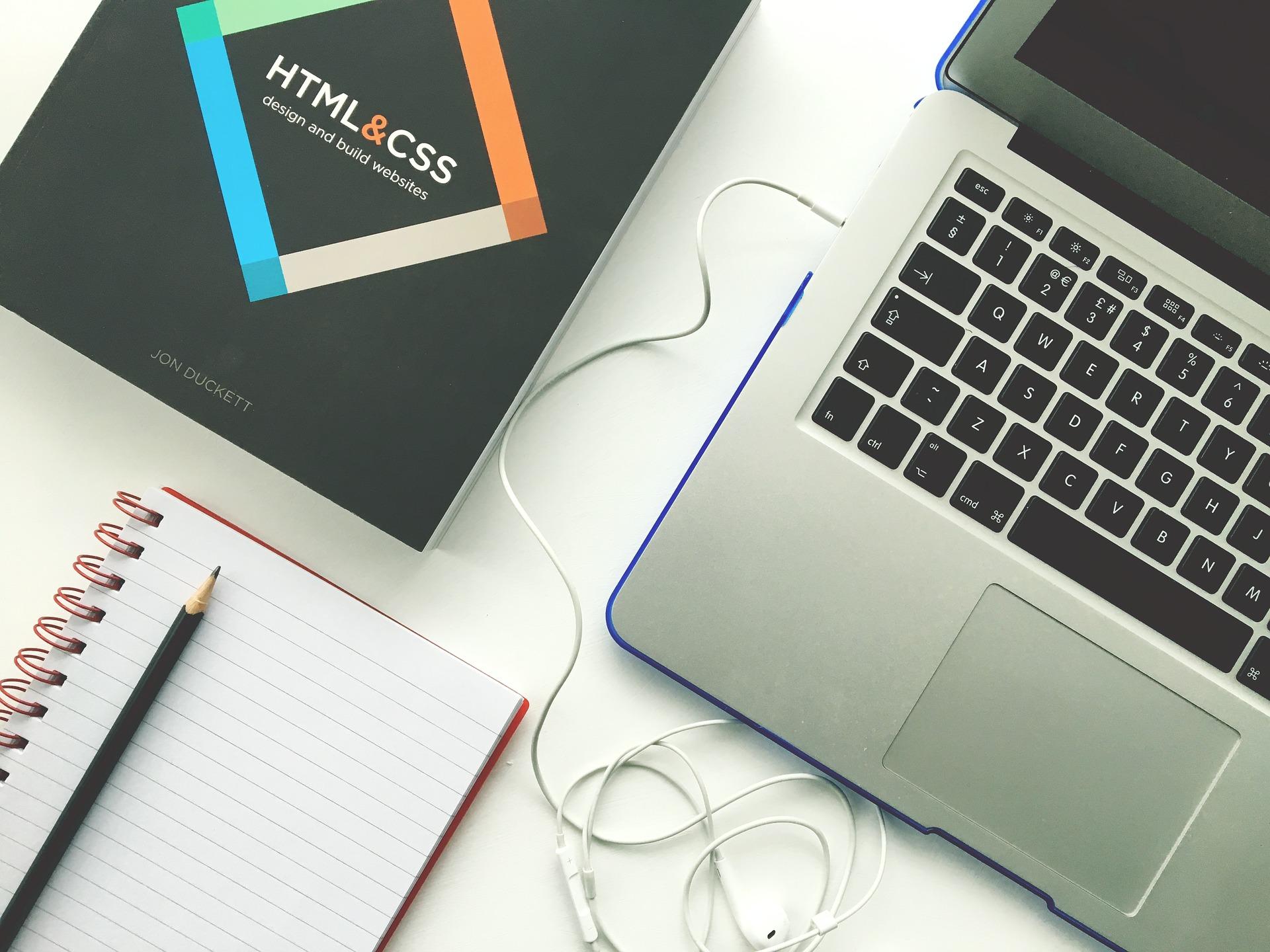 """Notebook com fone de ouvido conectado, caderno, lápis e livros com título """"HTML & CSS""""."""