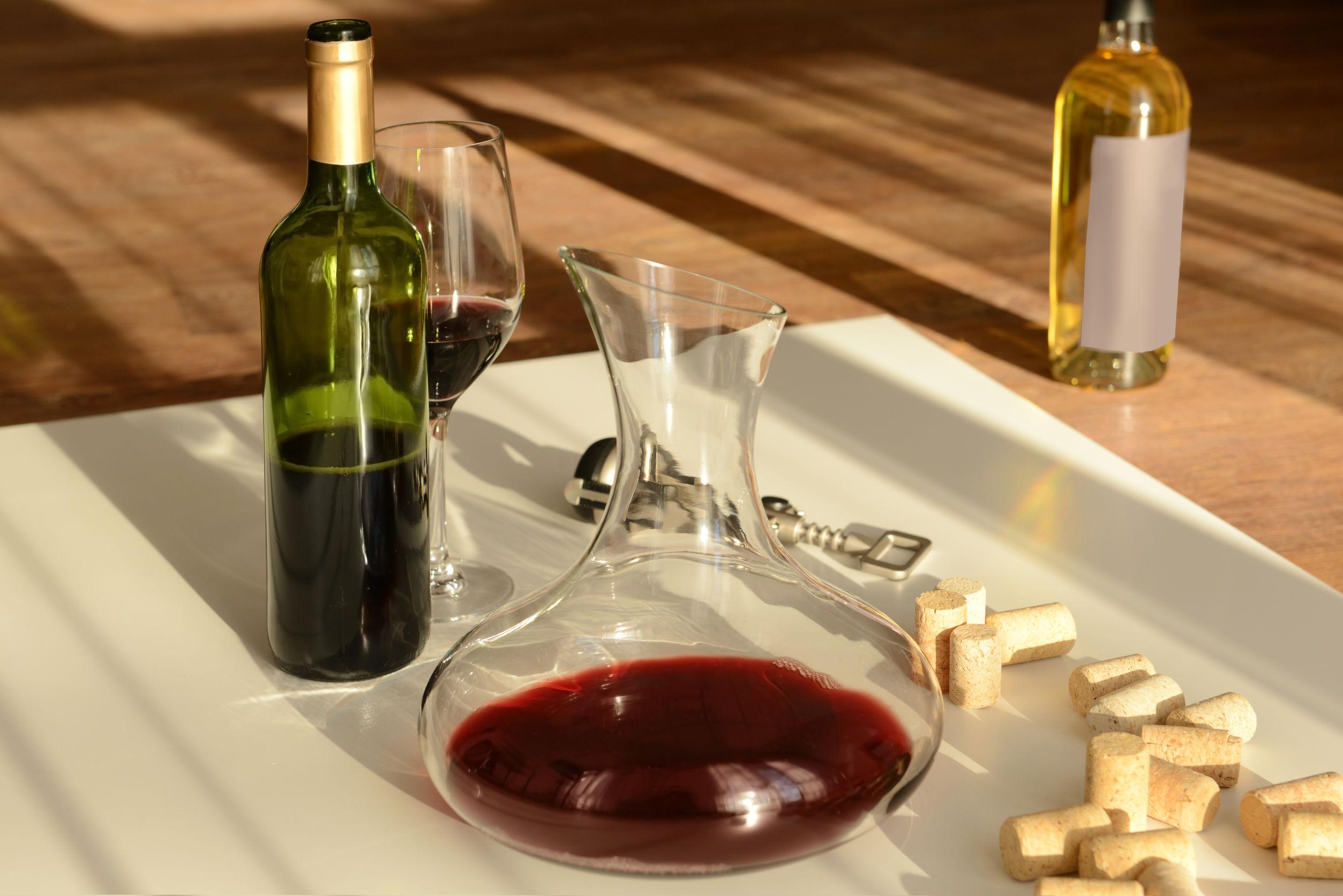 decanter de vinho em bancada com garrafas e rolhas