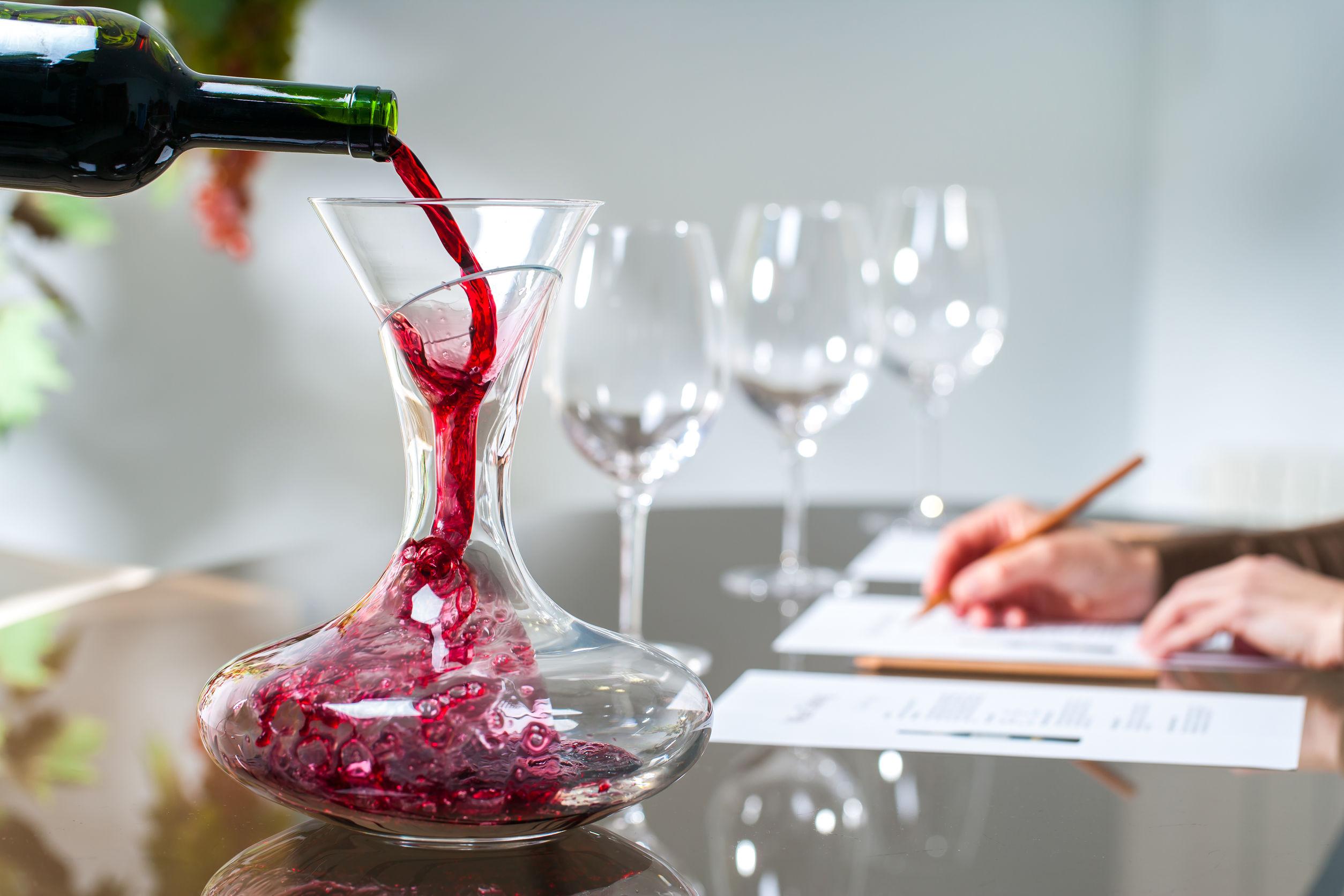Pessoa despejando vinho em um decanter