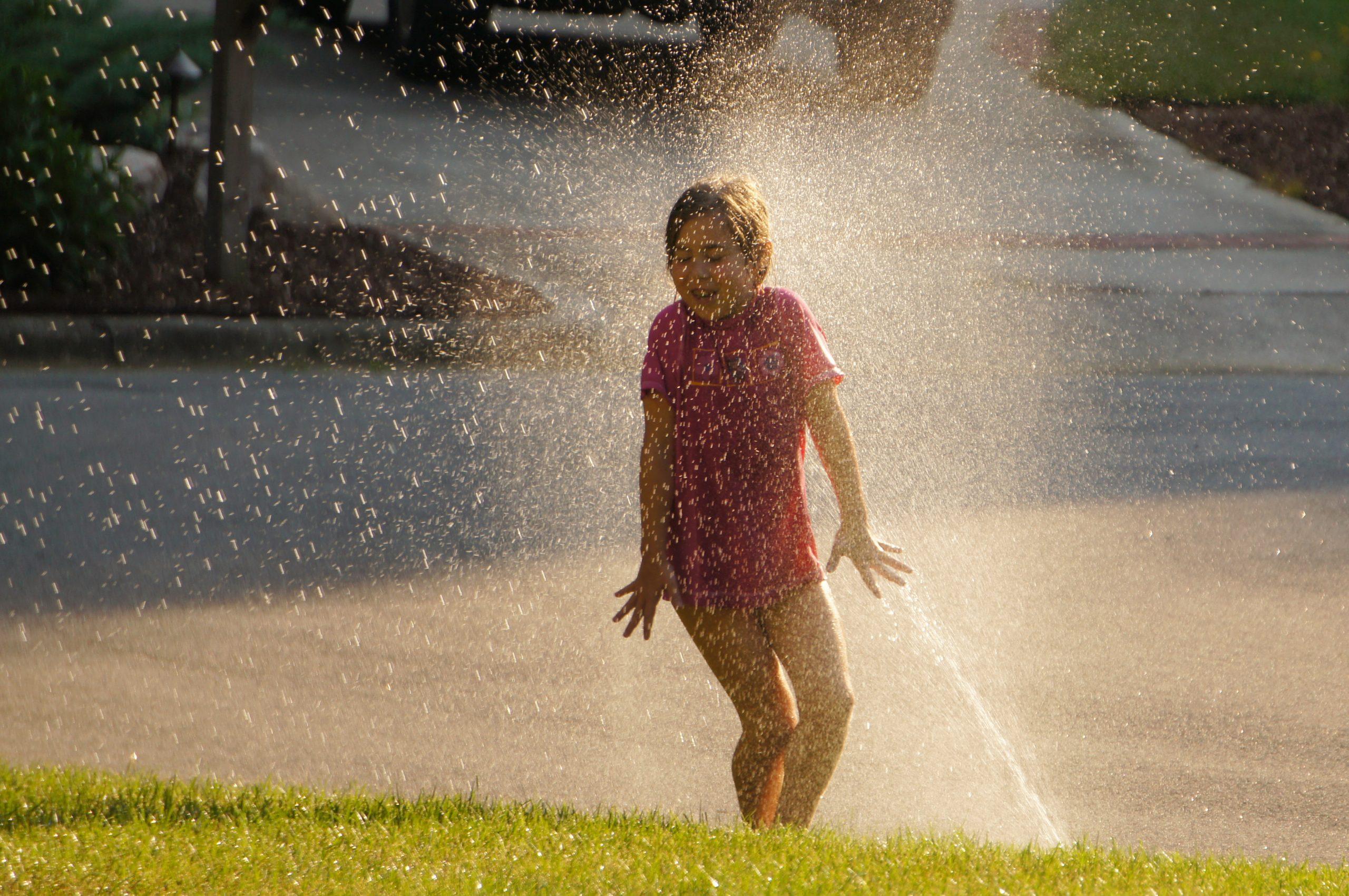 Criança sendo molhada por jato de água de um irrigador muito forte, igual uma chuva.