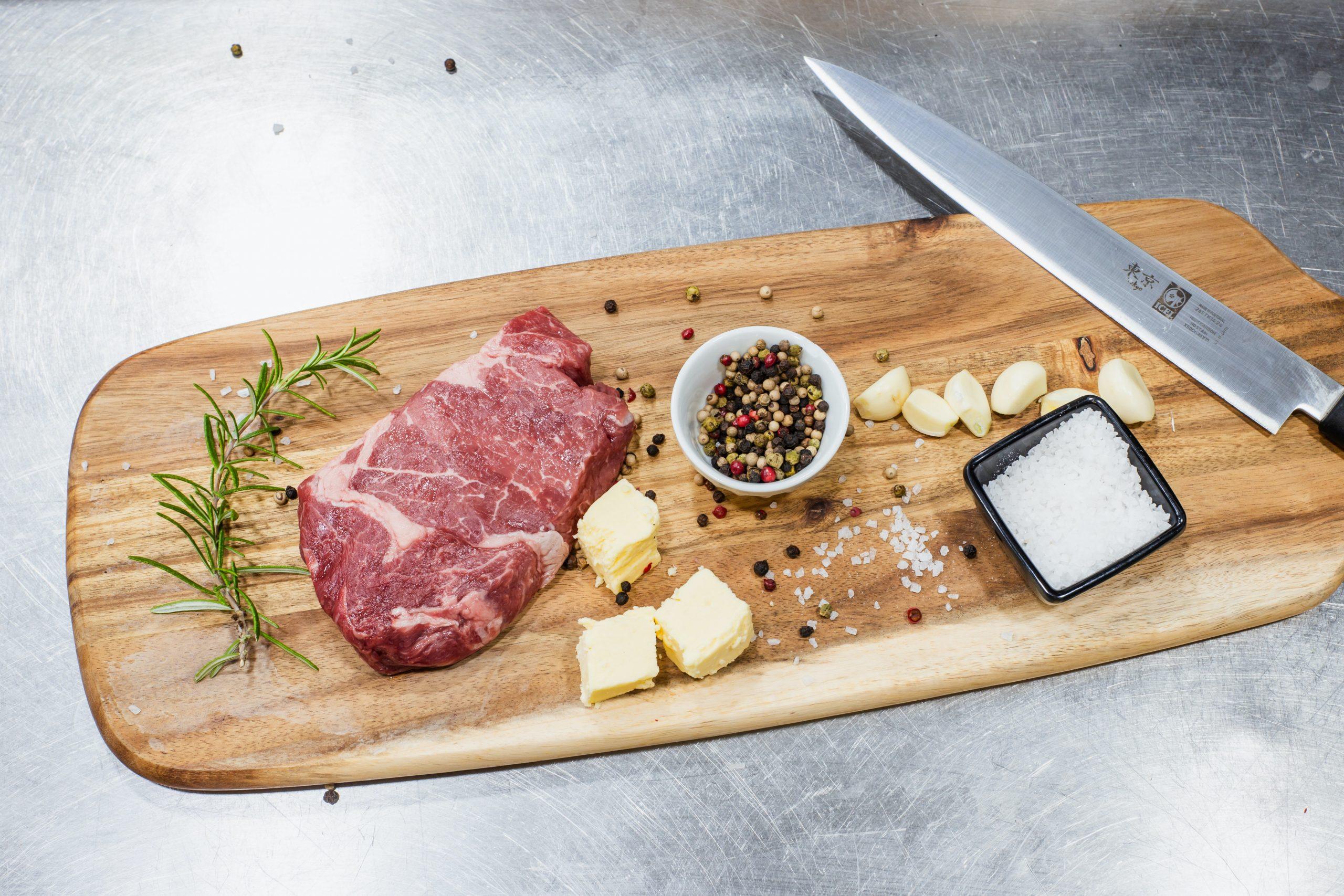 Na foto uma tábua de carne com um pedaço de carne, pimentas, sal e faca em cima.