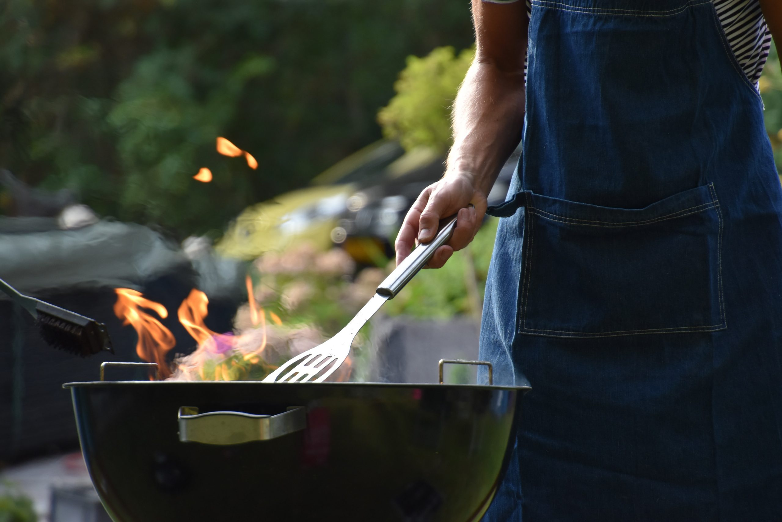 Na foto um homem usando avental na frente de uma churrasqueira.