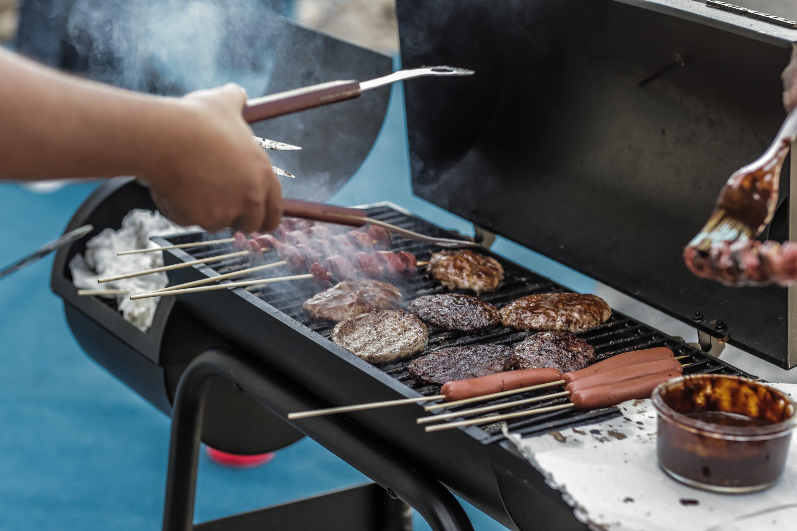 Na foto uma churrasqueira com hambúrgueres e salsichas e a mão de uma pessoa com um pegador.