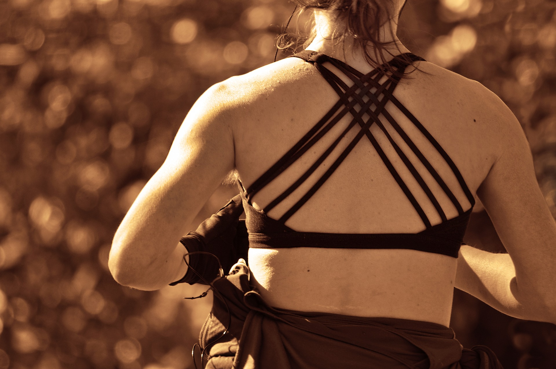 A imagem é uma mulher de costas correndo. Ela está usando uma roupa de academia preta e está com luvas nas mãos também.