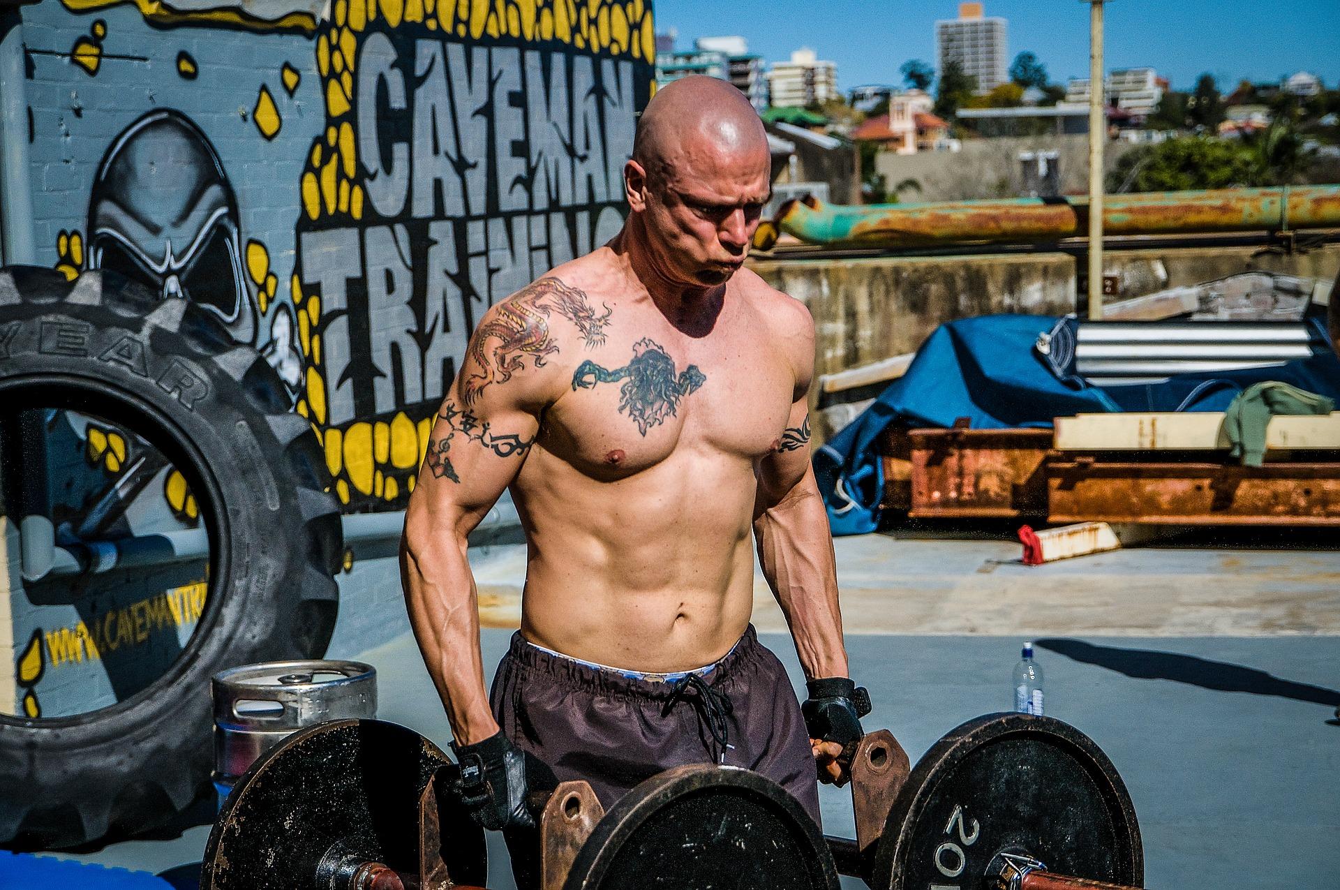 Um homem está em um local aberto fazendo exercícios físicos. Ele está fazendo levantamento de pesos maiores. Ele está sem blusa e usa luvas pretas nas mãos.