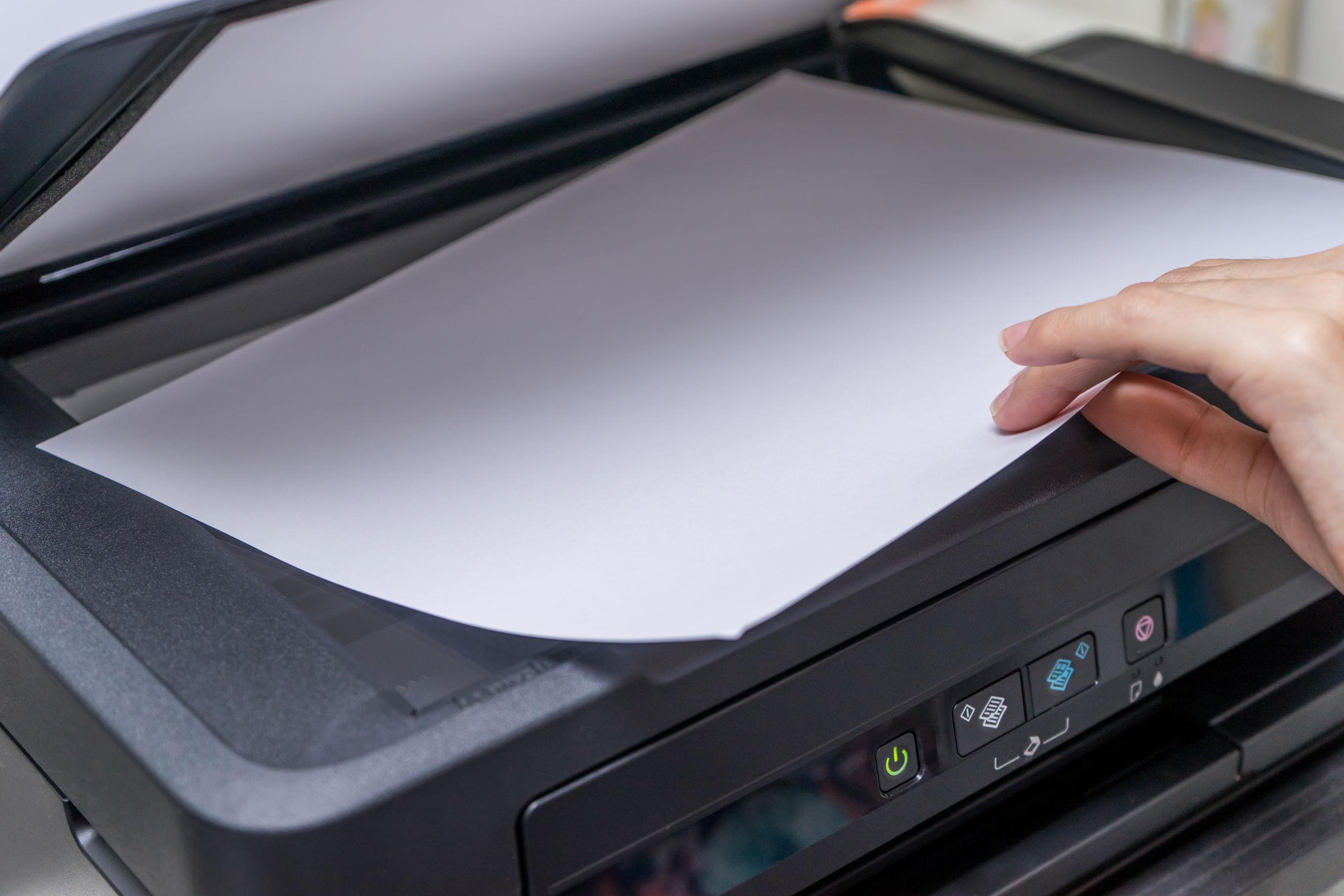 pessoa colocando papel em uma impressora multifuncional com melhor custo benefício