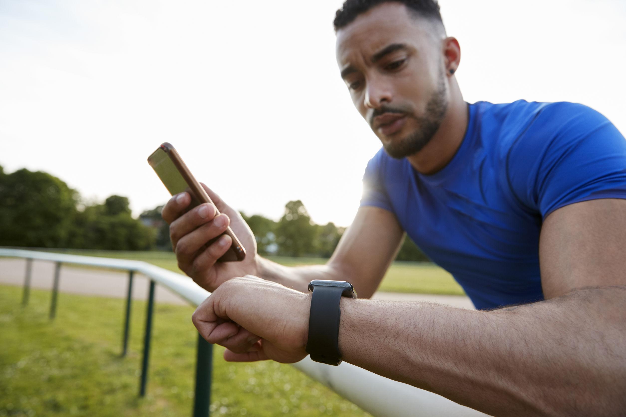 Homem utiliza smartwatch no punho esquerdo e confere resultados após exercício físico.