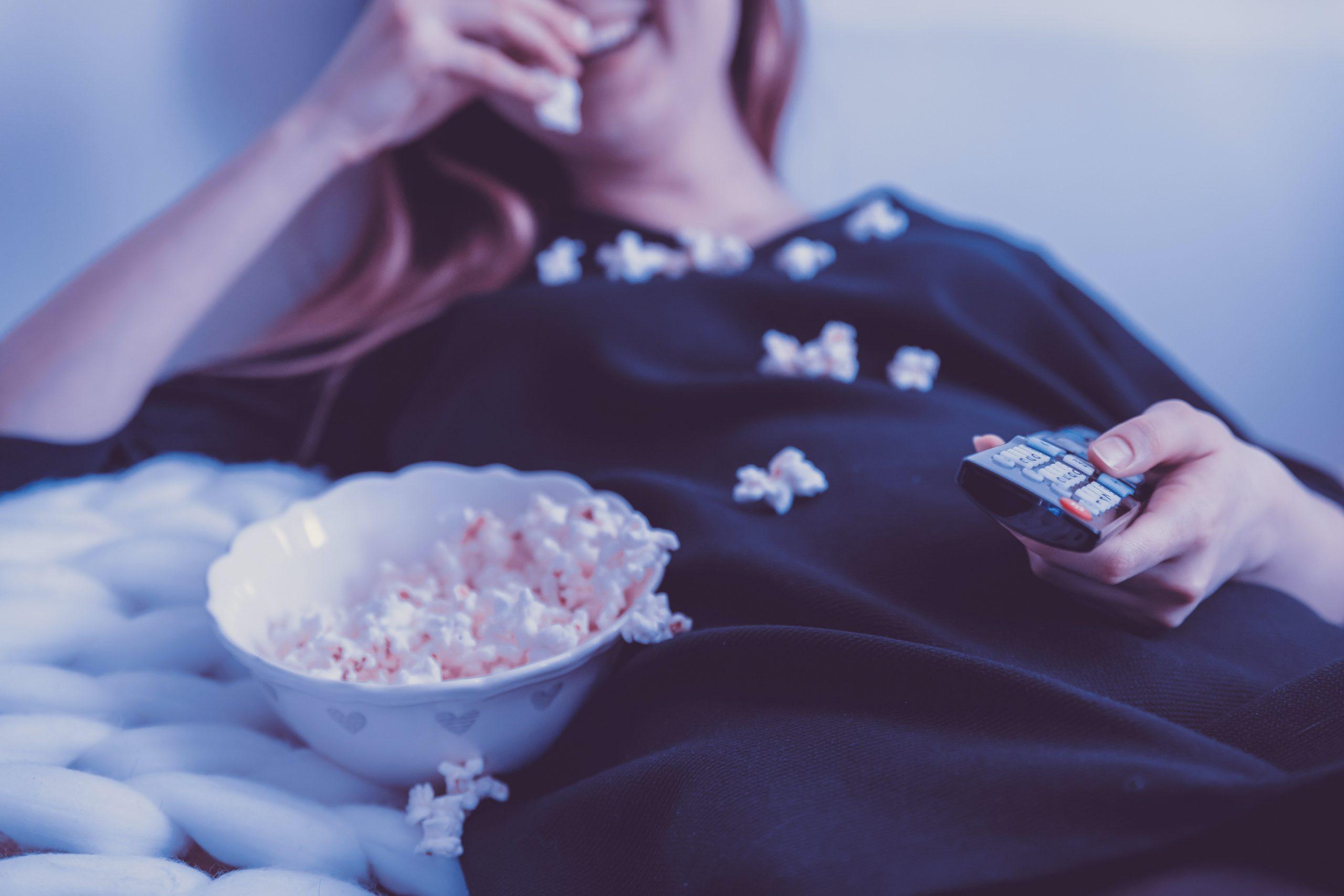 Imagem de uma mulher assistindo filme e comendo pipoca.