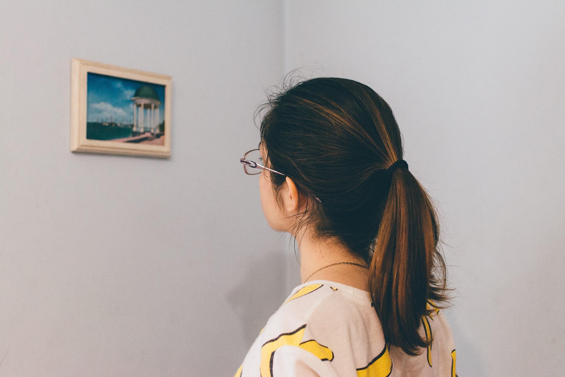 Mulher olhando porta retrato de parede.