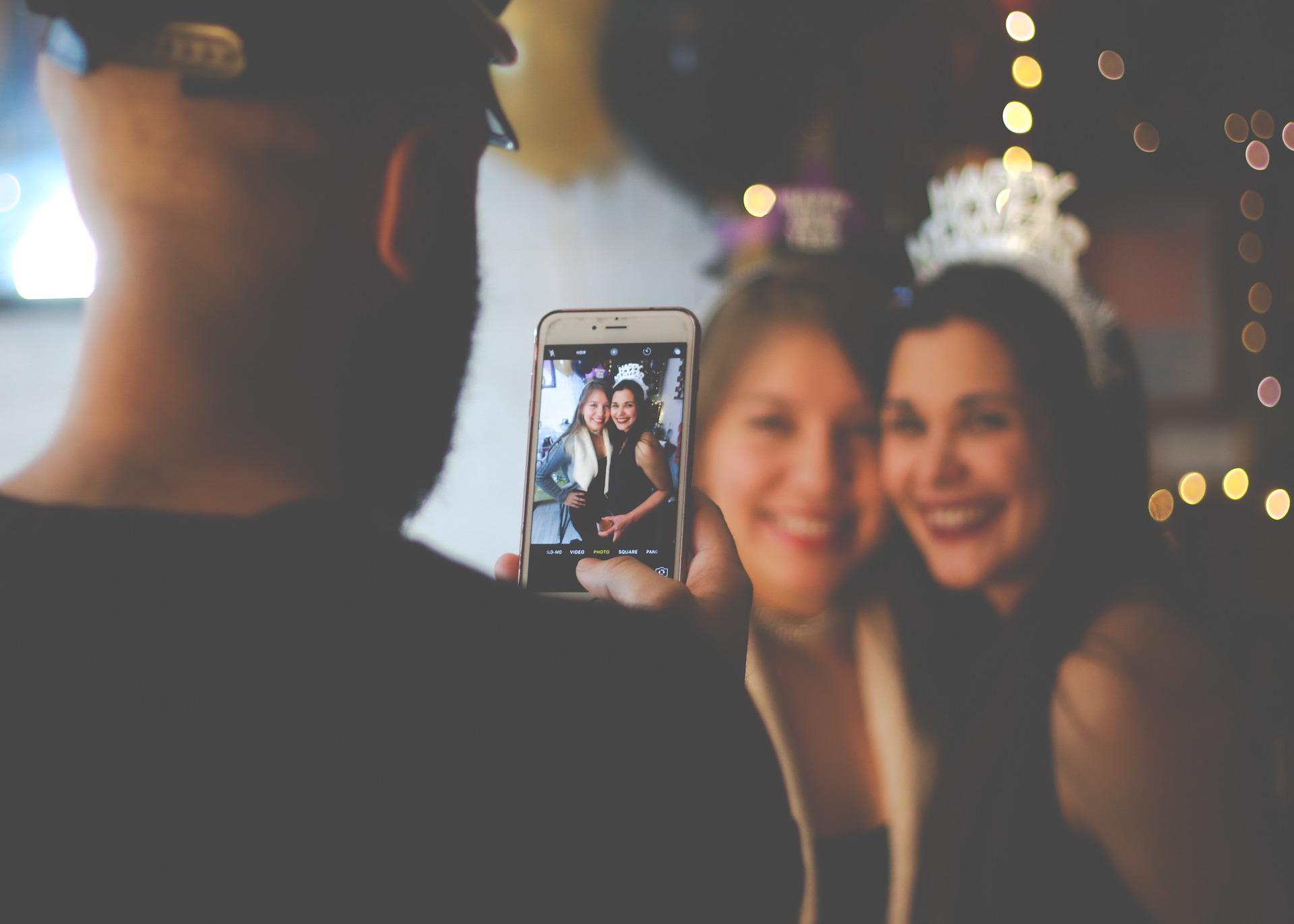 Homem tirando foto com o celular de duas mulheres abraçadas.
