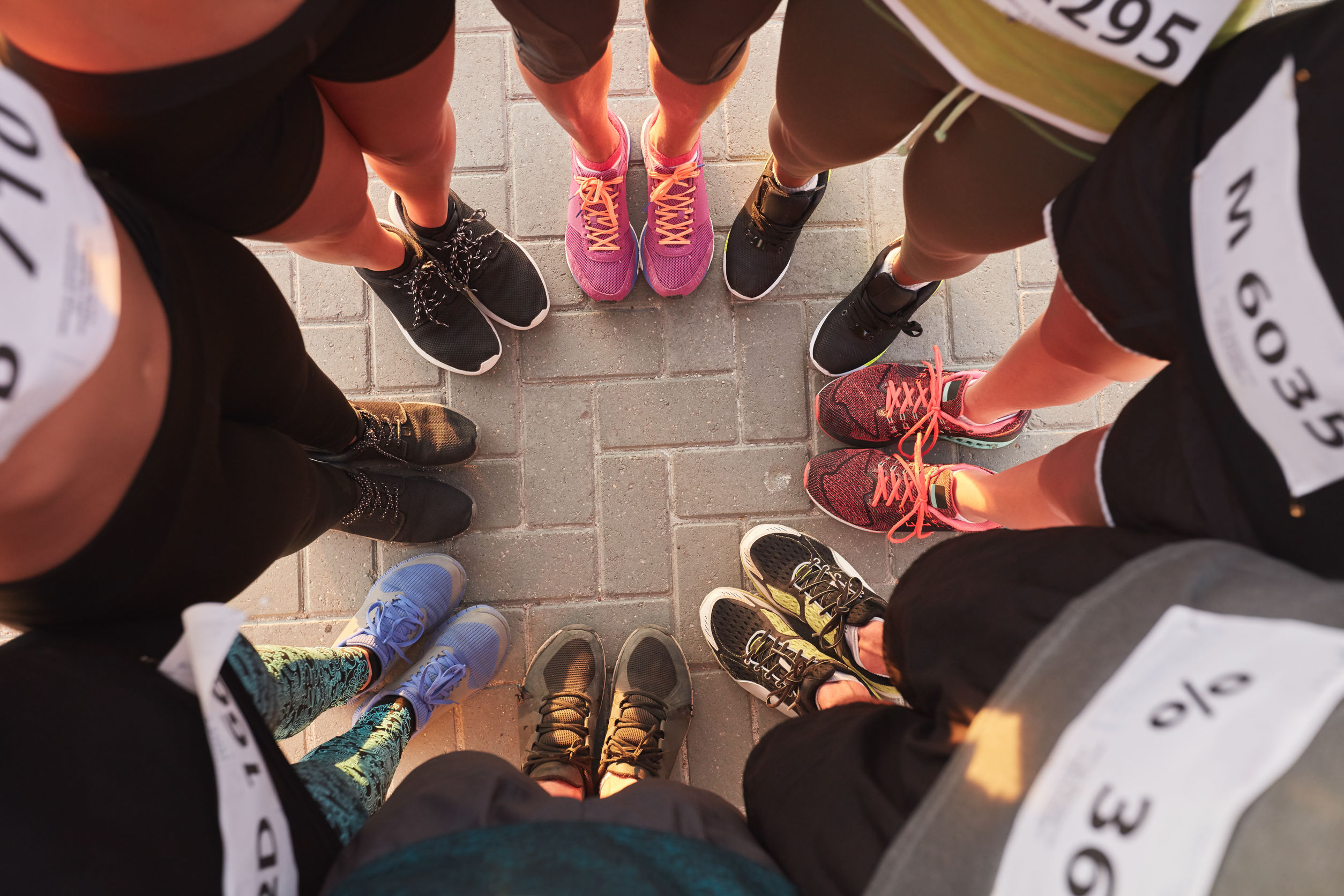 grupo de pessoas usando tênis para corrida