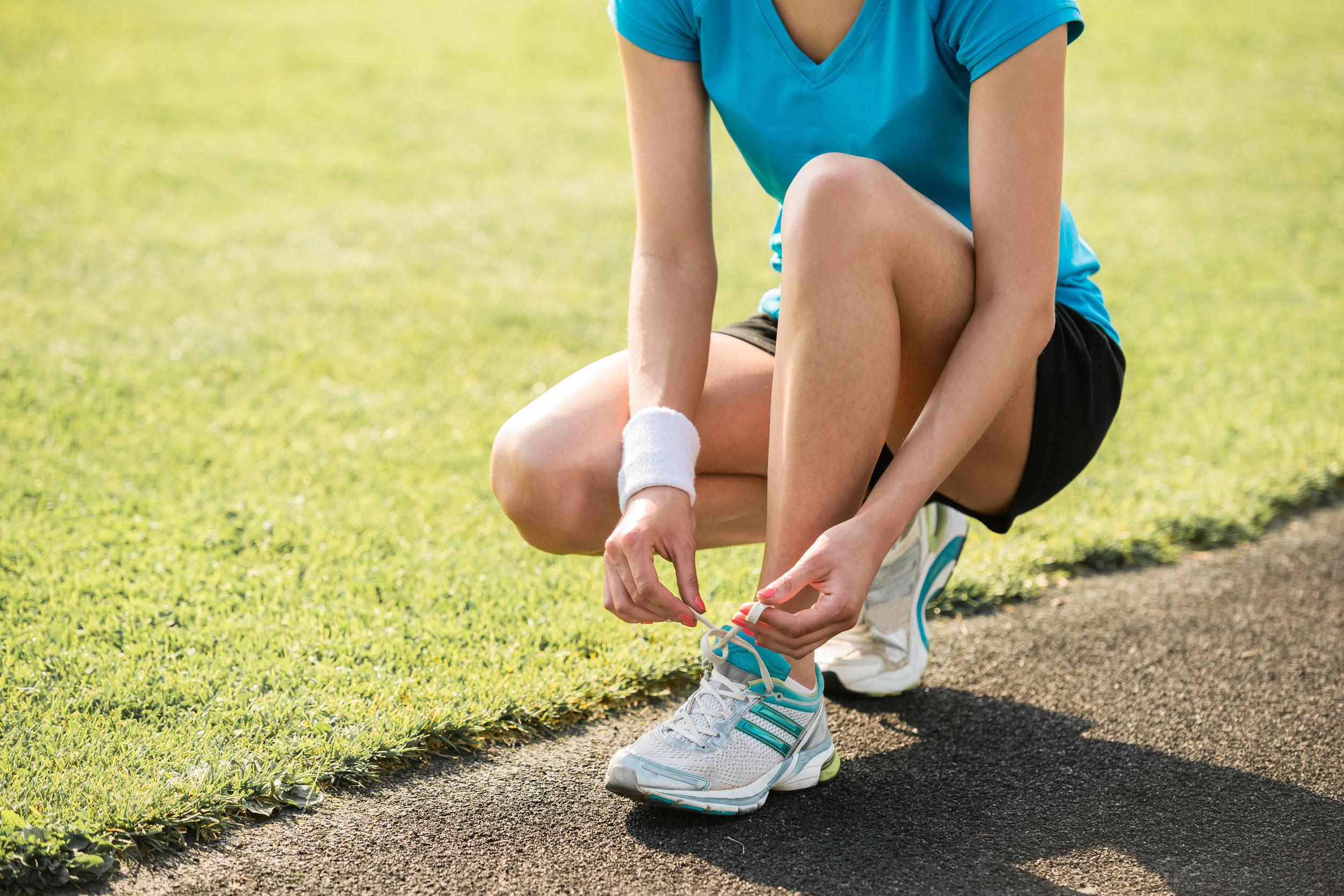 mulher amarrando o tênis de corrida
