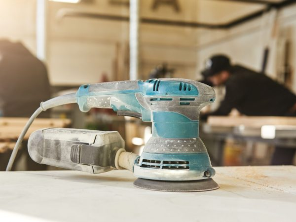 Electric Sander. Machine for grinding wood. Wood processing in the carpentry workshop. Horizontal shot