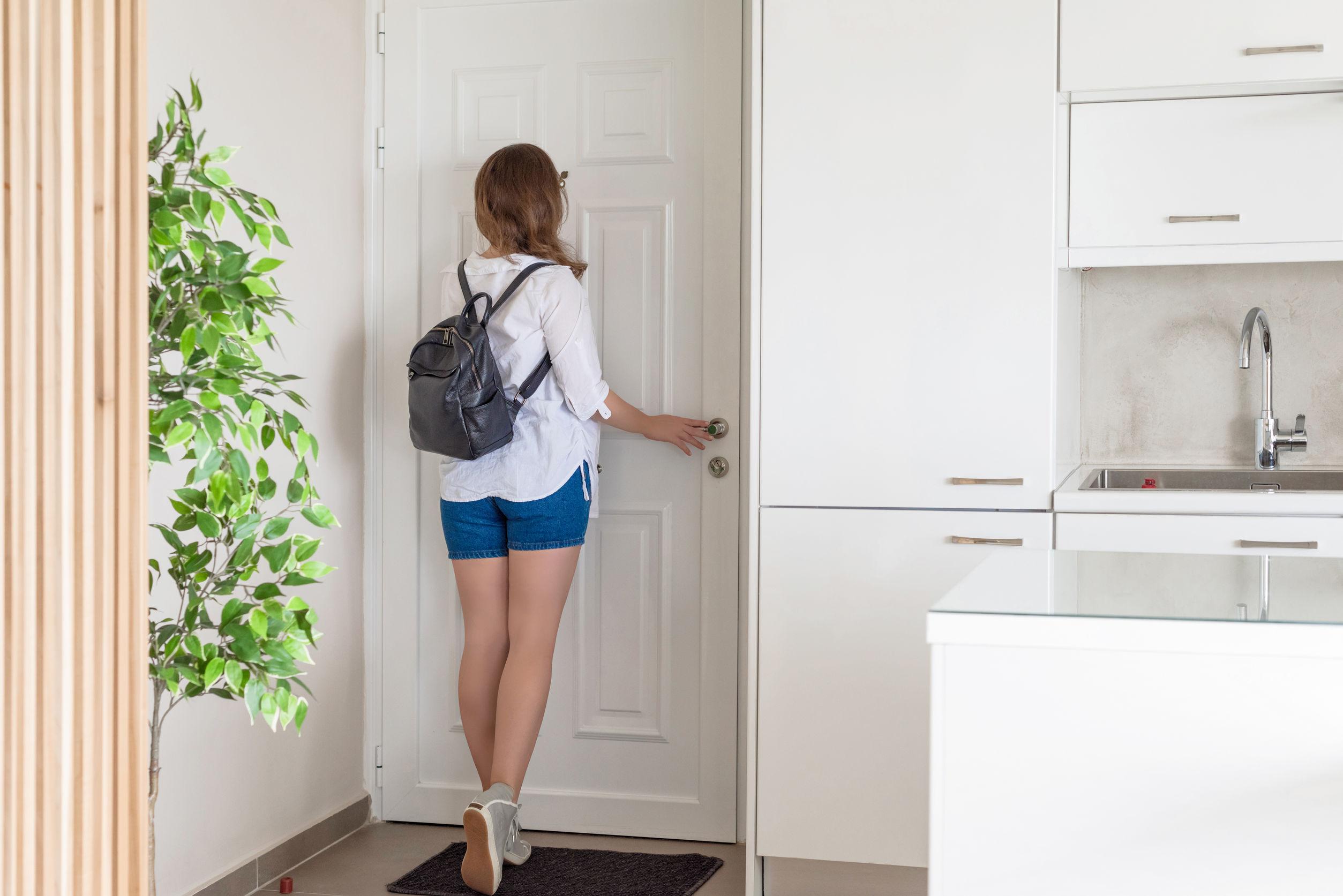 Mulher em uma cozinha olhando no olho mágico da porta