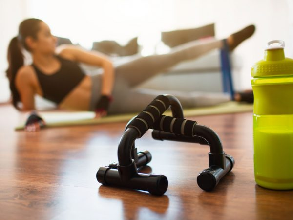 Young woman doing sport workout in room during quarantine. Green protein bottle and push ups hand bar in front. Girl exercising using resistance band. Stretch left leg up and forward